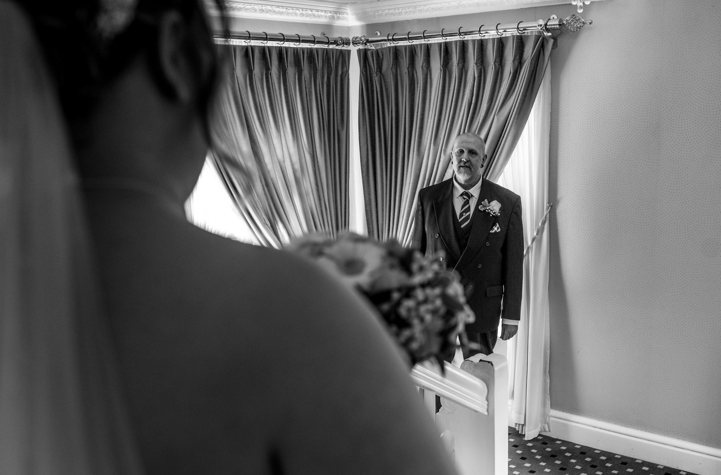 A view over the brides shoulder of the father of the bride seeing her for the first time.