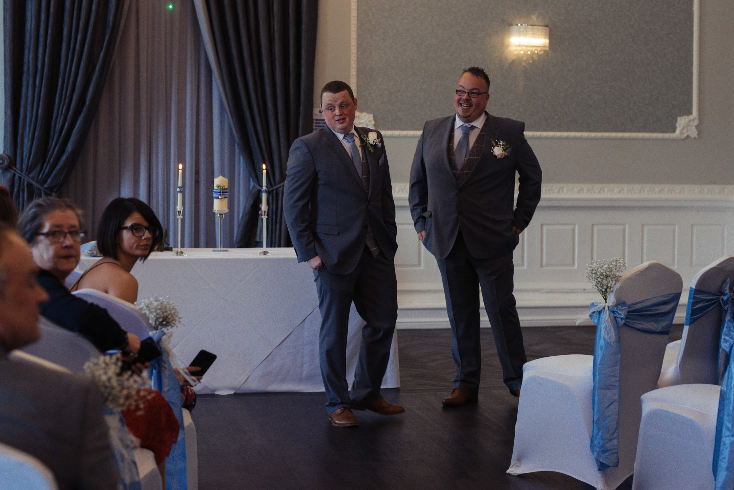 The groom and best man stand at the top of the aisle to wait for the bride.