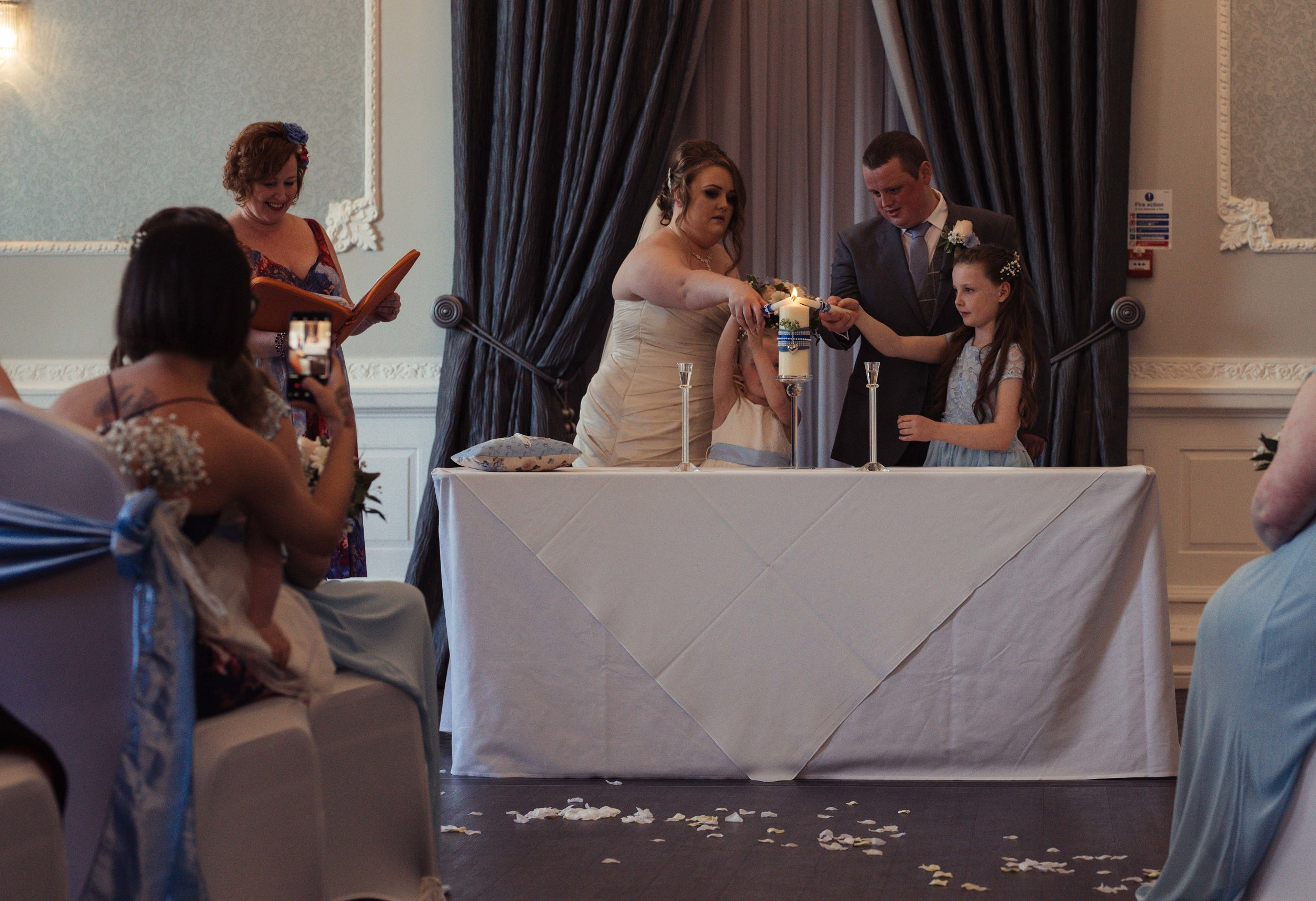 The bride and groom and their two children light candles during the wedding ceremony