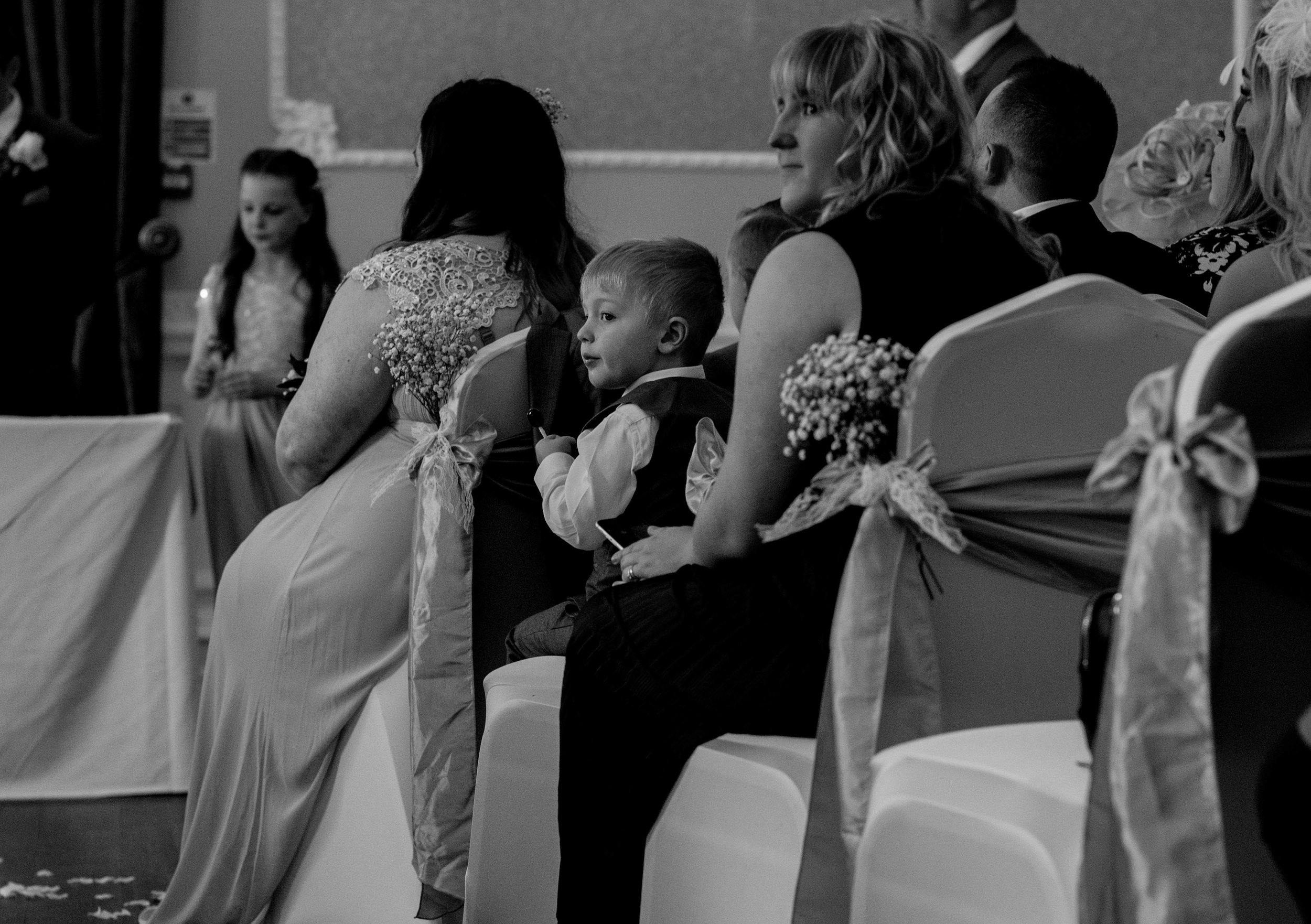 A young page boy sits quietly during the wedding ceremony