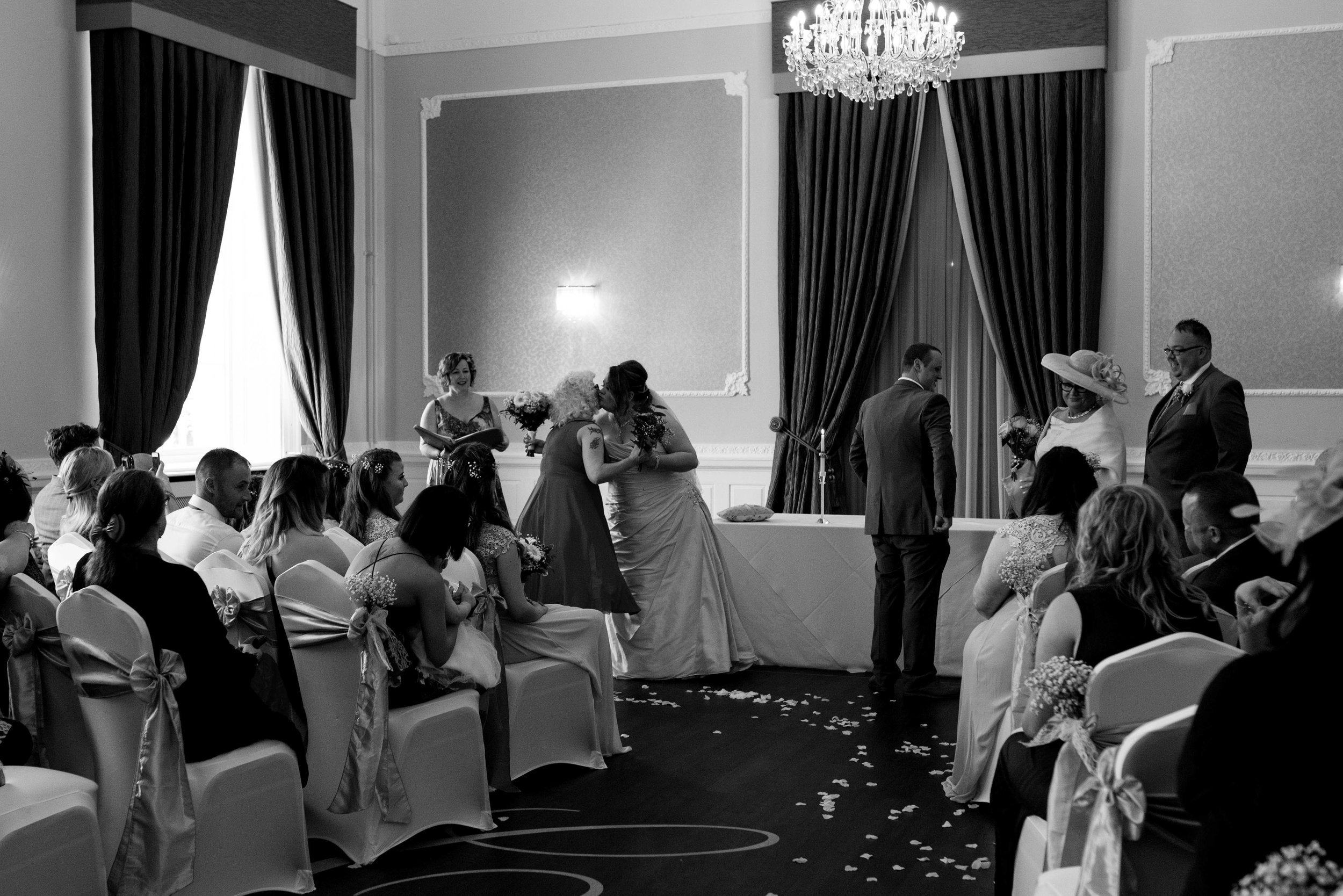 The bride and groom gift their mothers flowers during the wedding ceremony