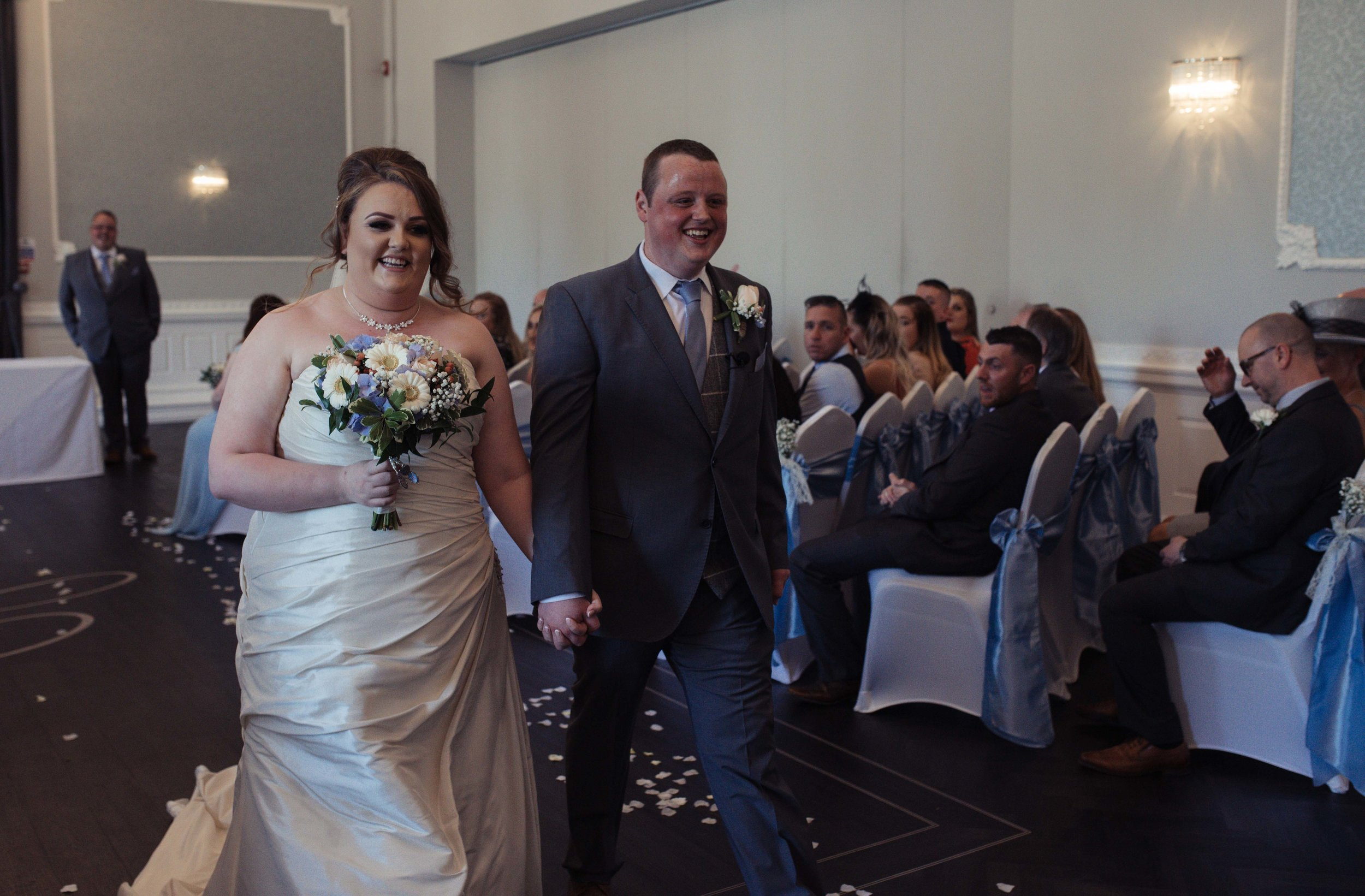 Smiling bride and groom walk out of the ceremony venue together, holding hands