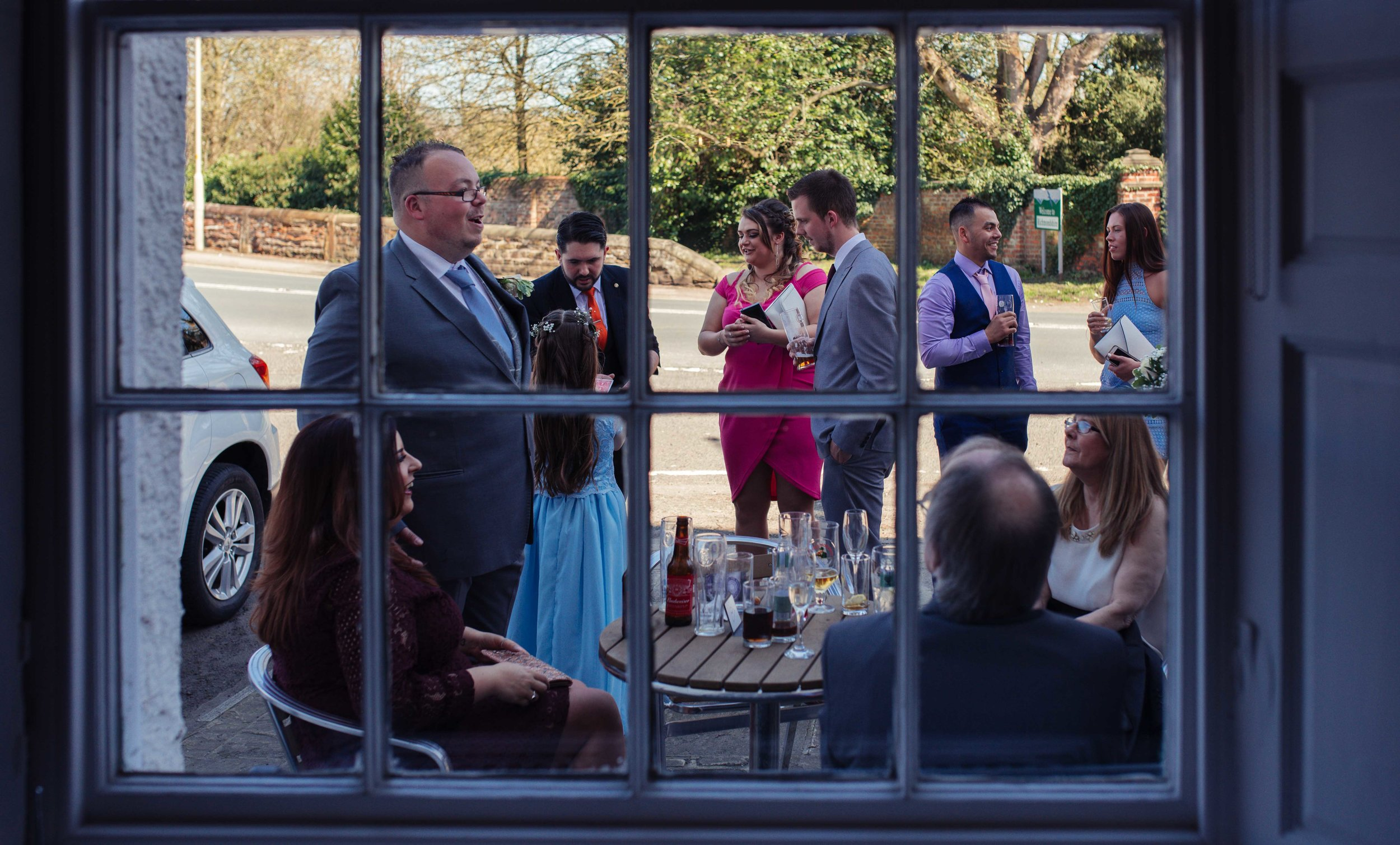 Guests assemble outside the venue in the sunshine