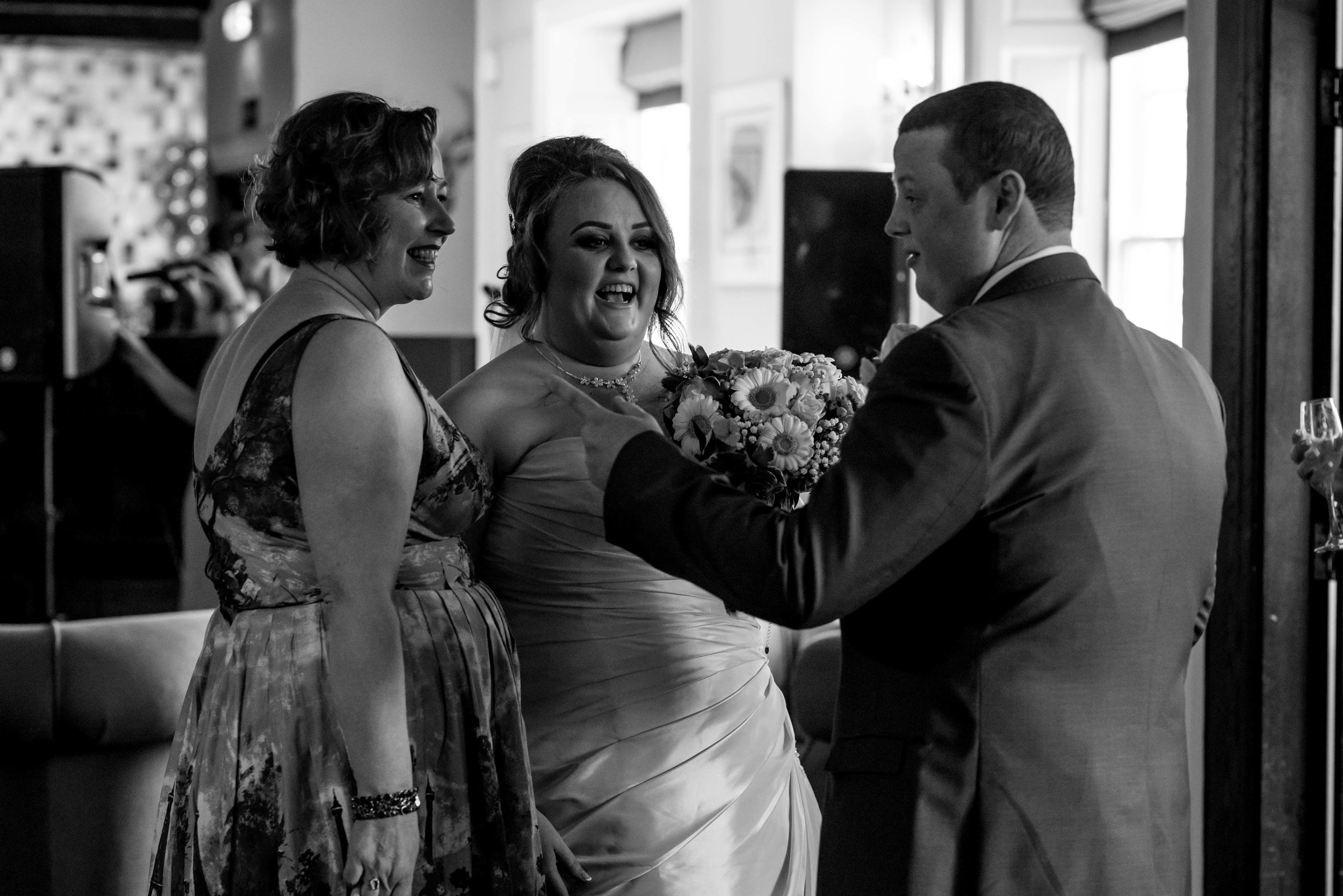 The bride and groom share a laugh with a wedding guest straight after their wedding ceremony