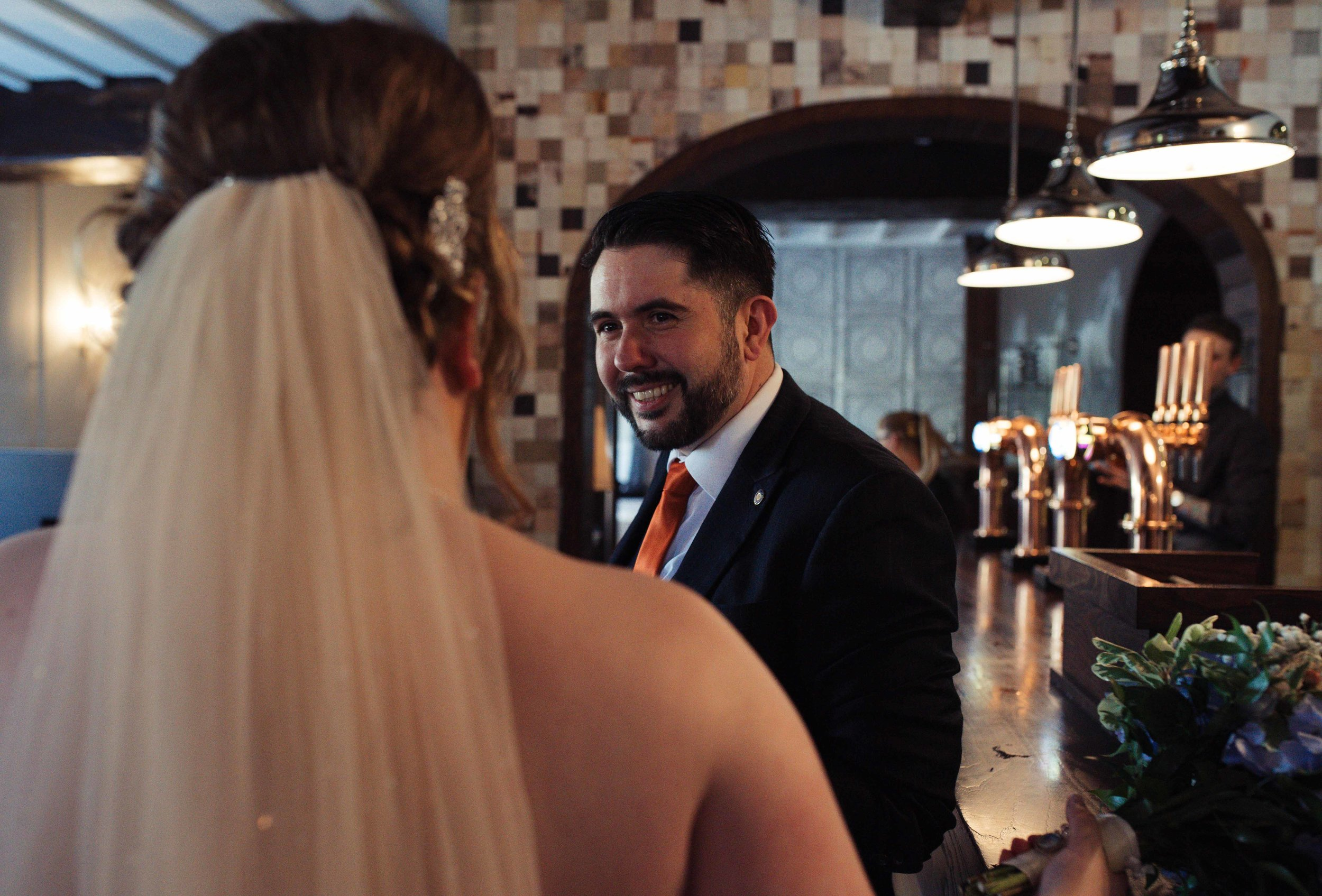 Male wedding guest stands at the bar and chats with the bride