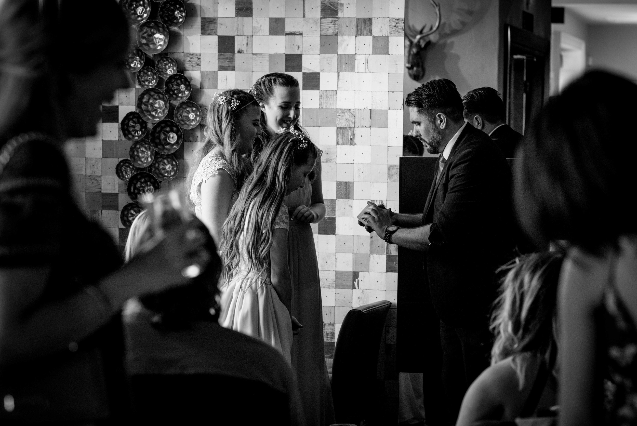 The young wedding guests watch with amazement the magician doing card tricks