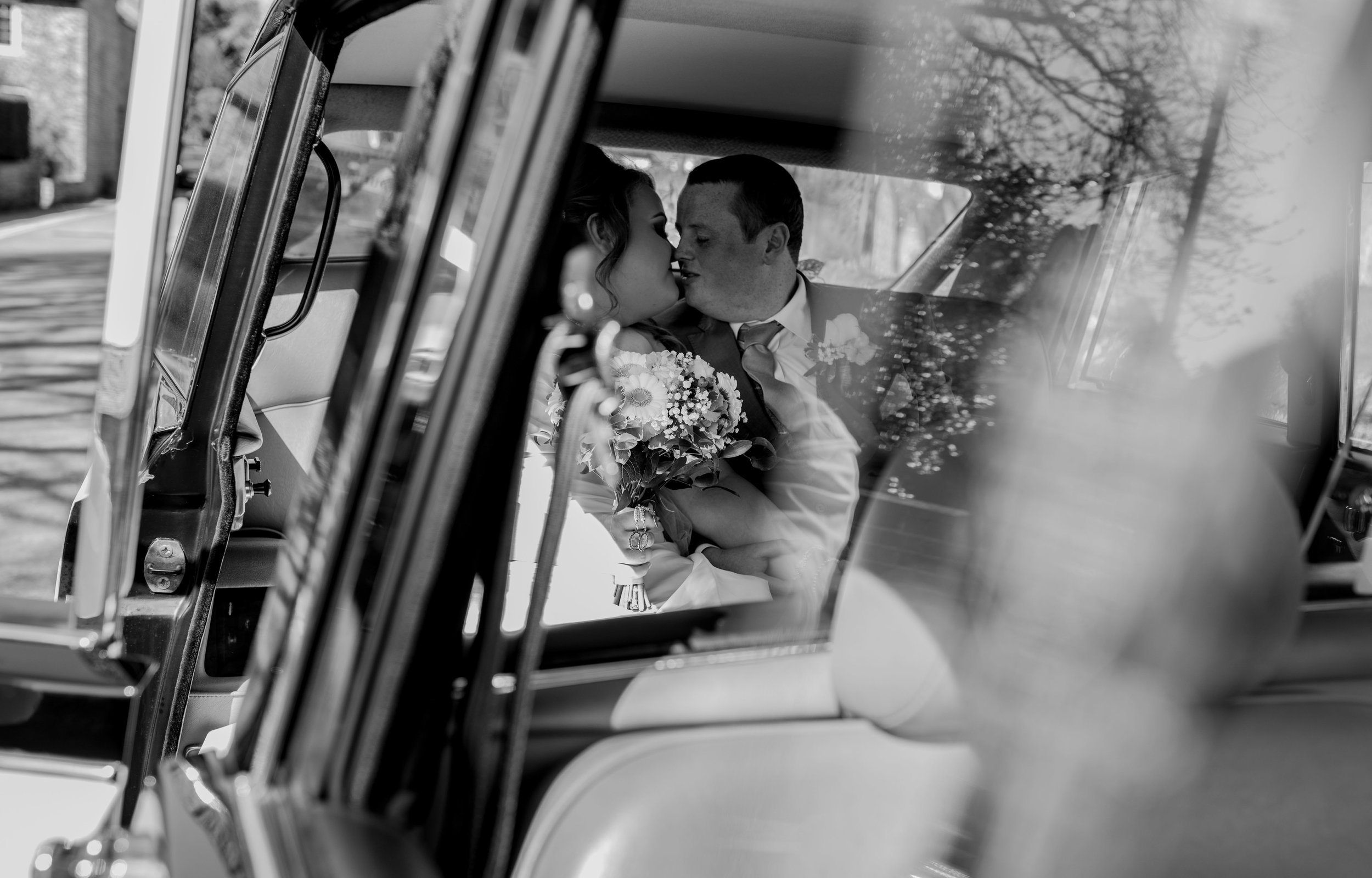 Bride and groom share a kiss in the back of the wedding car