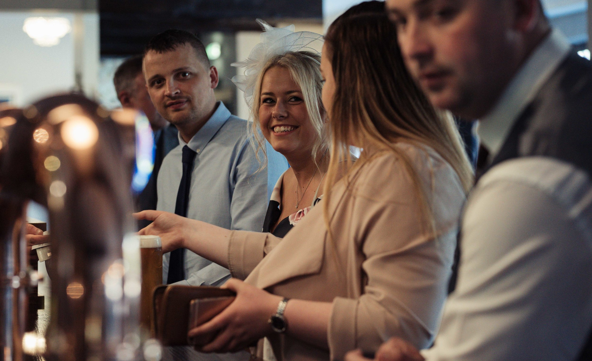 Guests stand at the bar waiting to be served, but share a smile for the camera