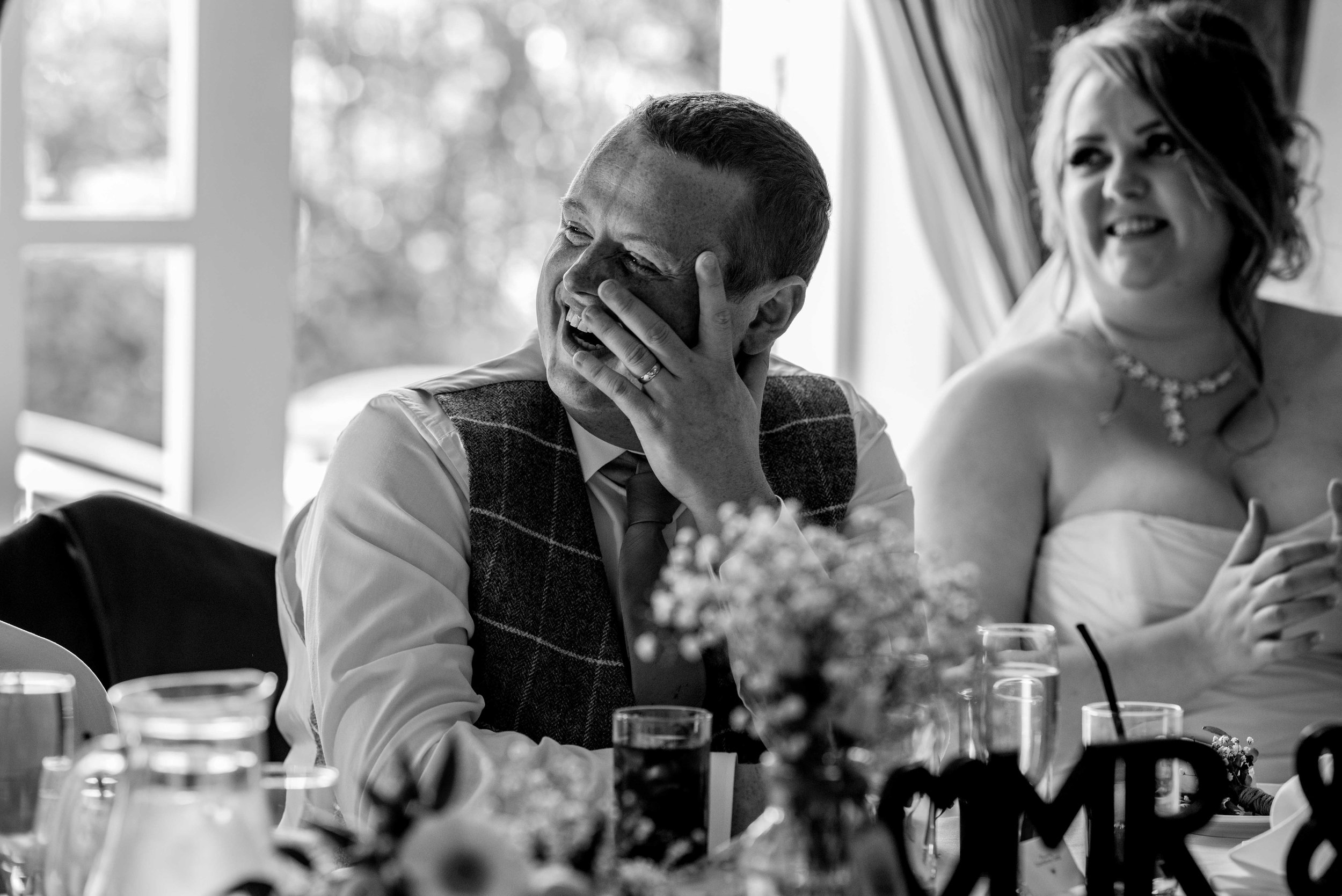 The groom sits looking awkward and a bit worried during the best mans speech