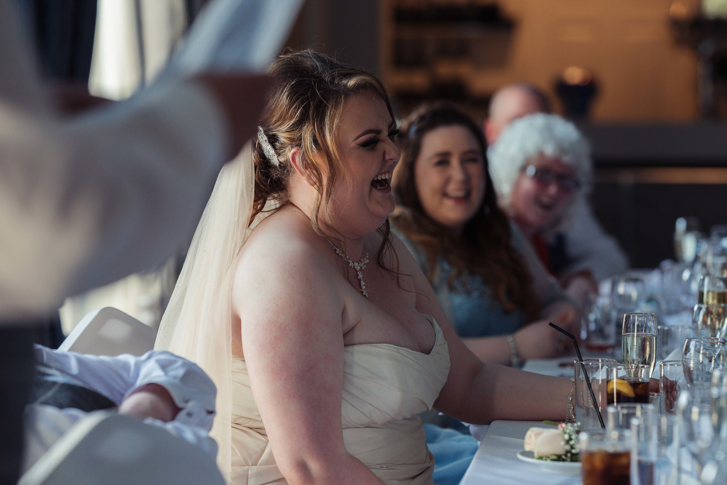 The bride has a huge laugh during one of the wedding soeeches