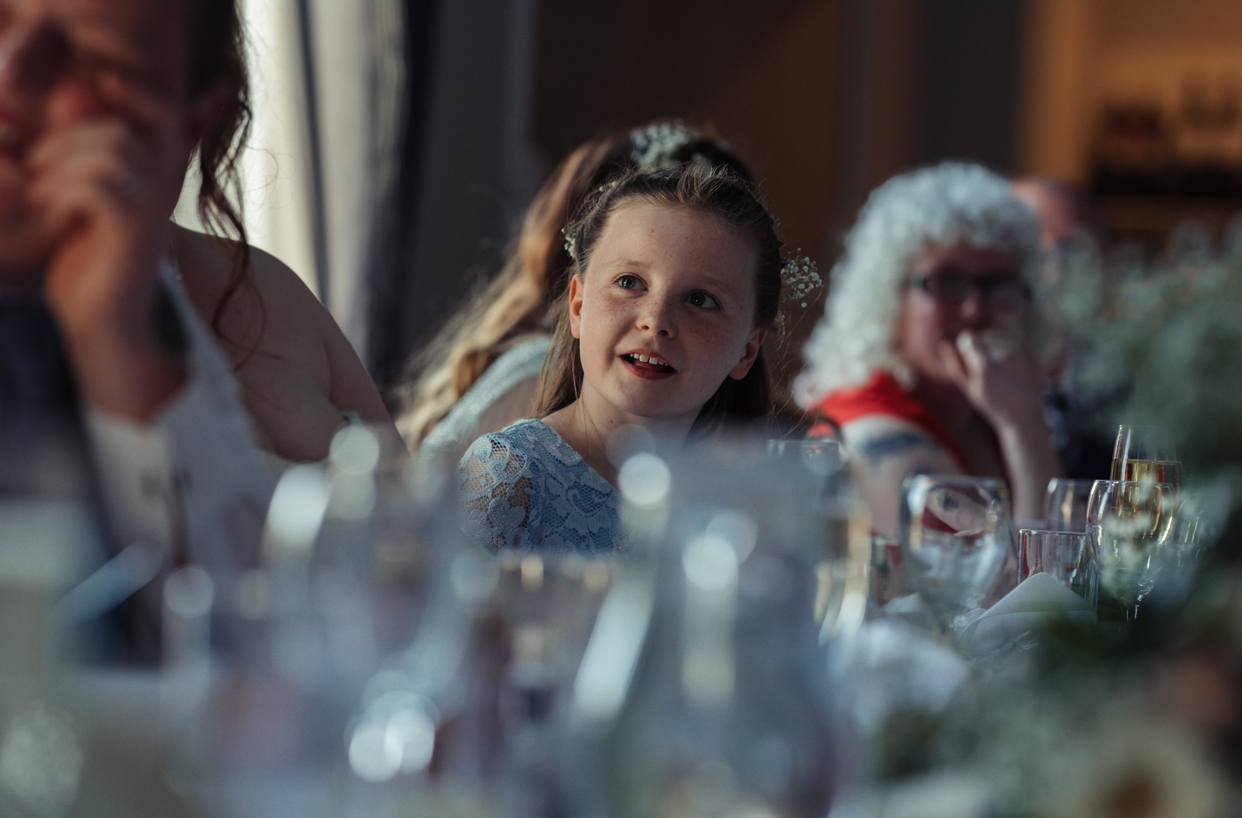 The bride and grooms daughter has a smile while she is being talked about during the wedding speeches