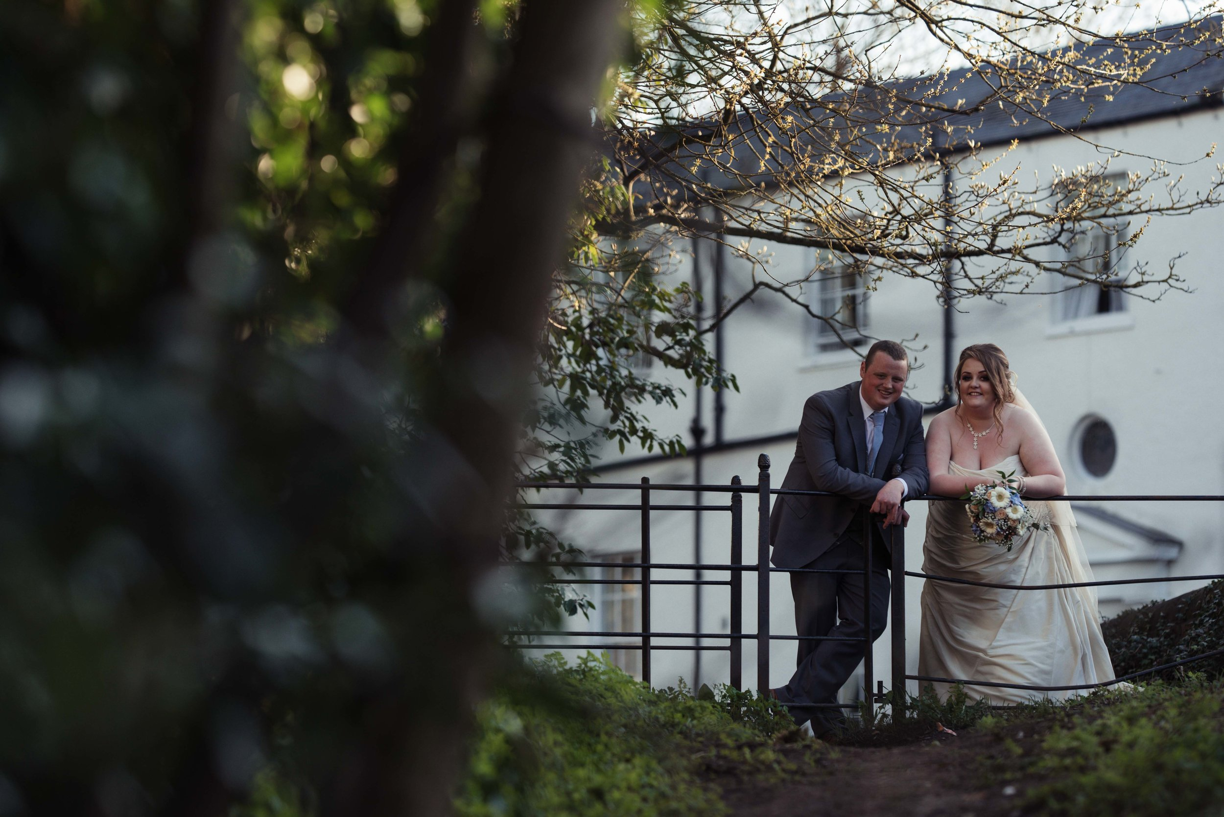 The bride and groom lean on a fence during their wedding photography