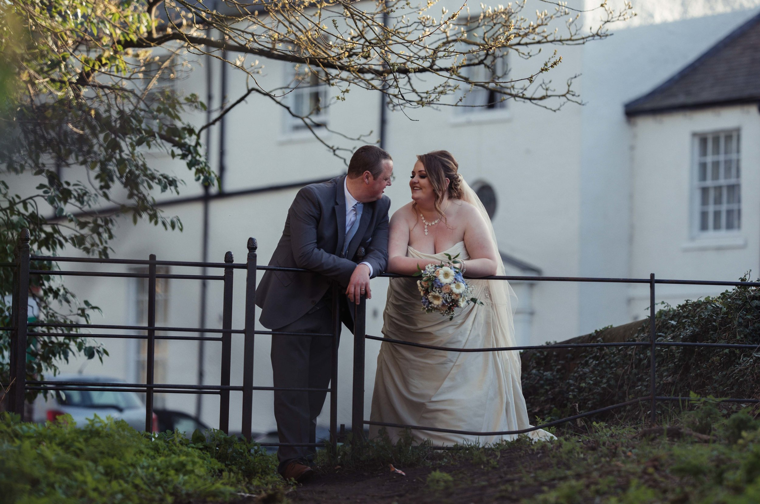 The bride and groom stand and chat to each other, with their wedding venue in view in the background