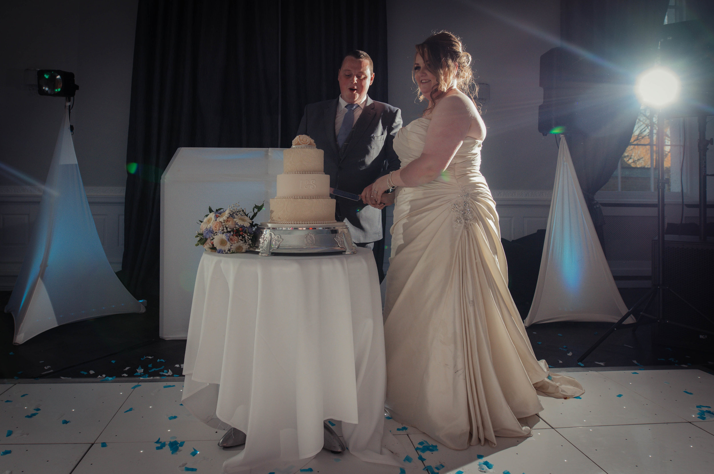 The bride and groom stand to cut their wedding cake together