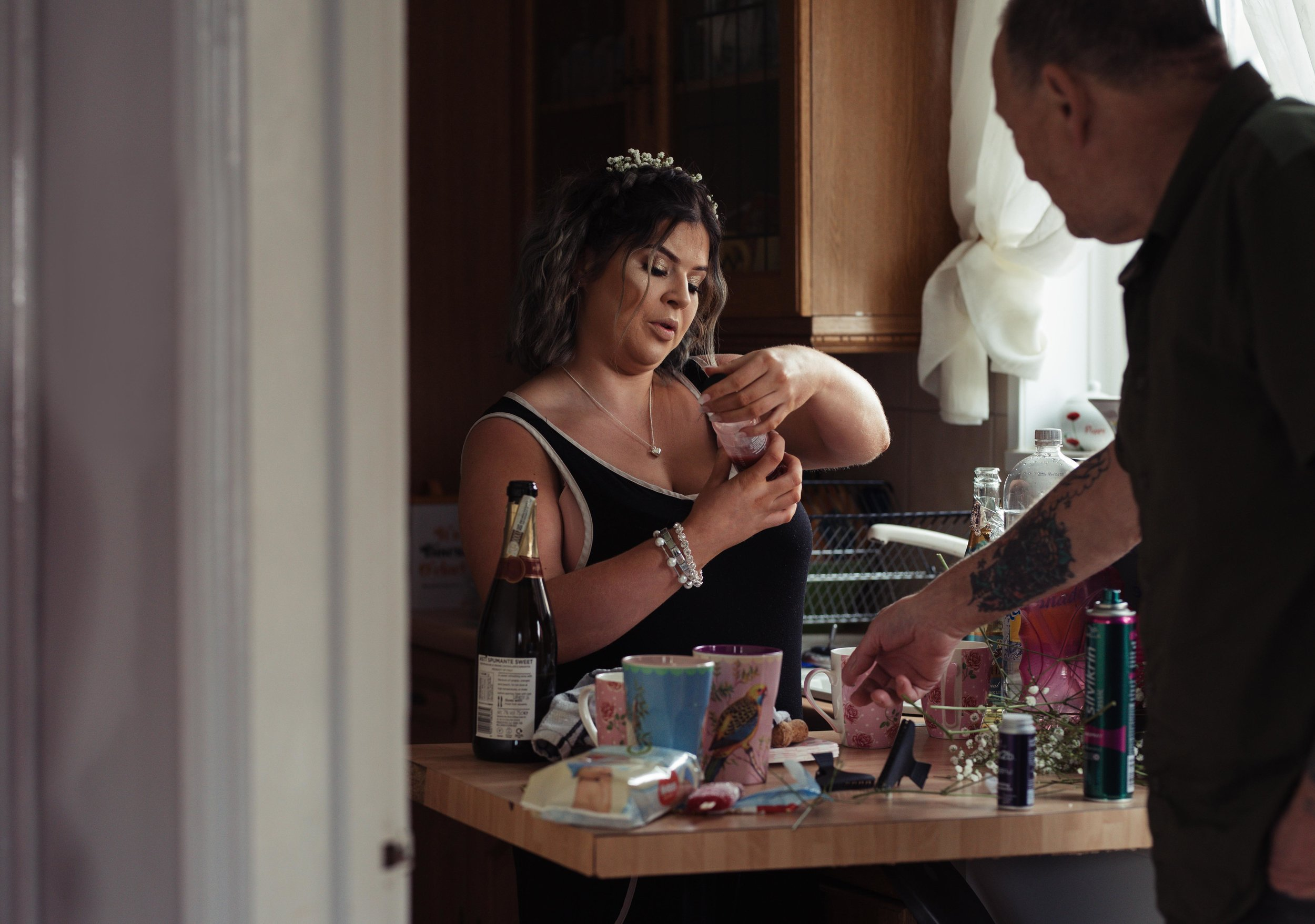 One of the bridesmaids looks at her nail varnish in the kitchen