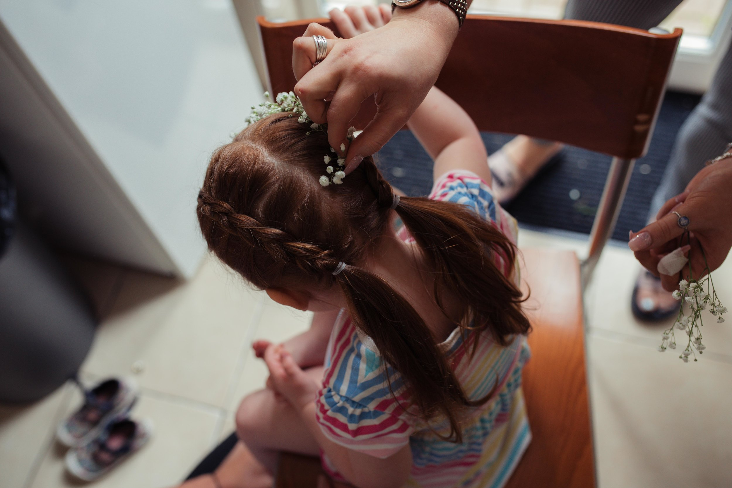 Flower girl has flowers put in her hair while she sits in the kitchen