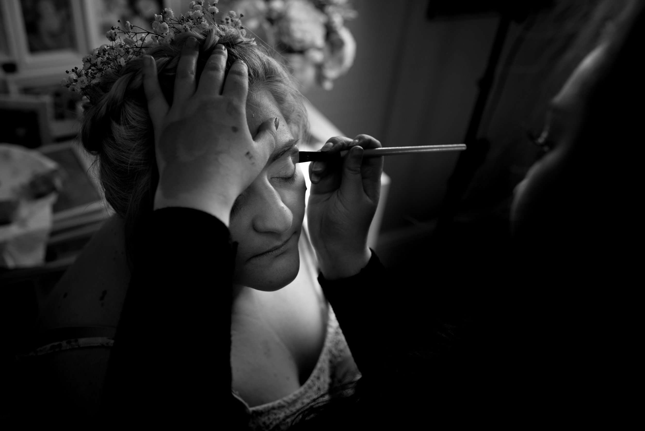 Black and white image of the bride getting her makeup done before the wedding