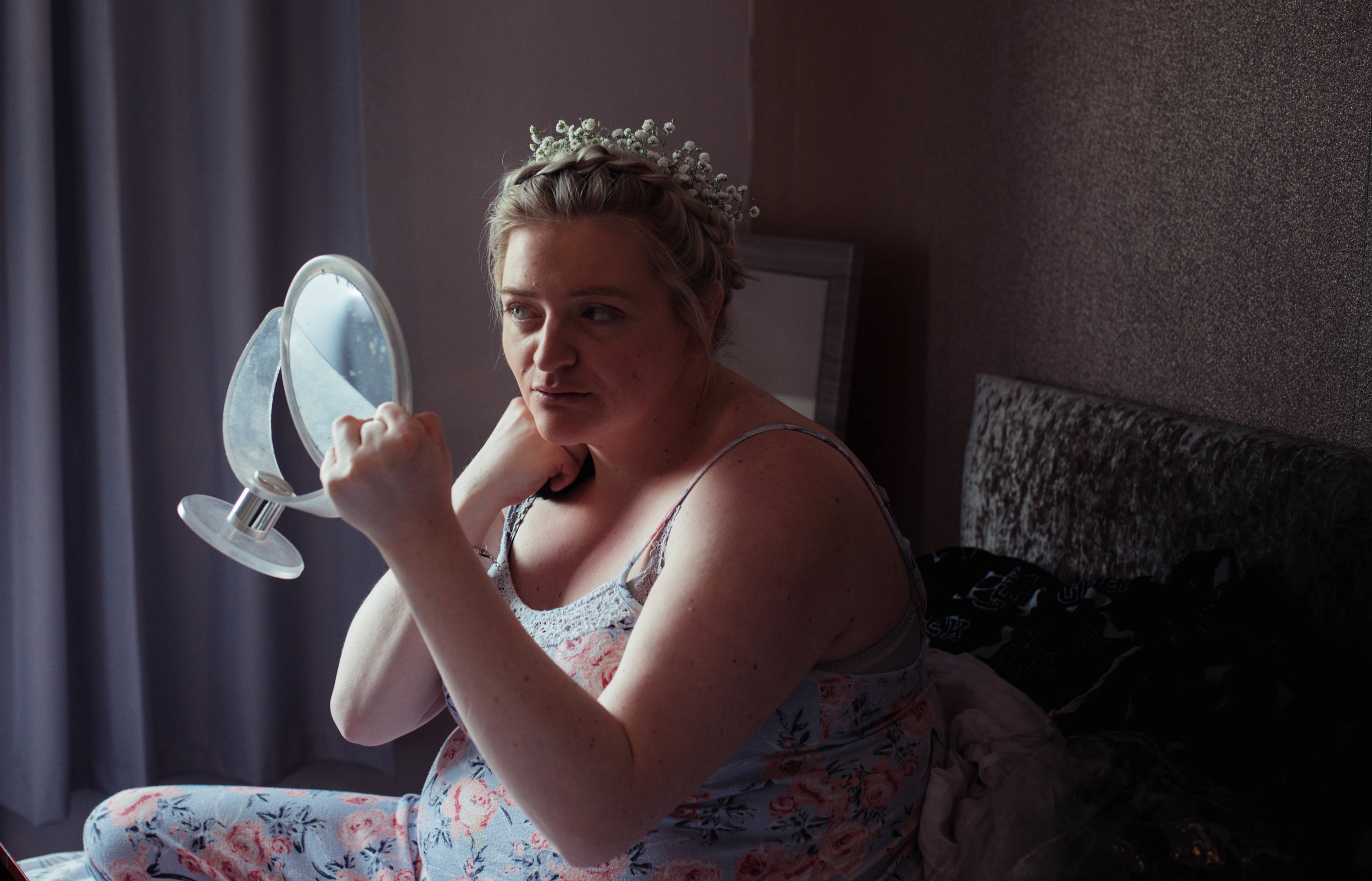 The bride sits on her bed to finish her makeup