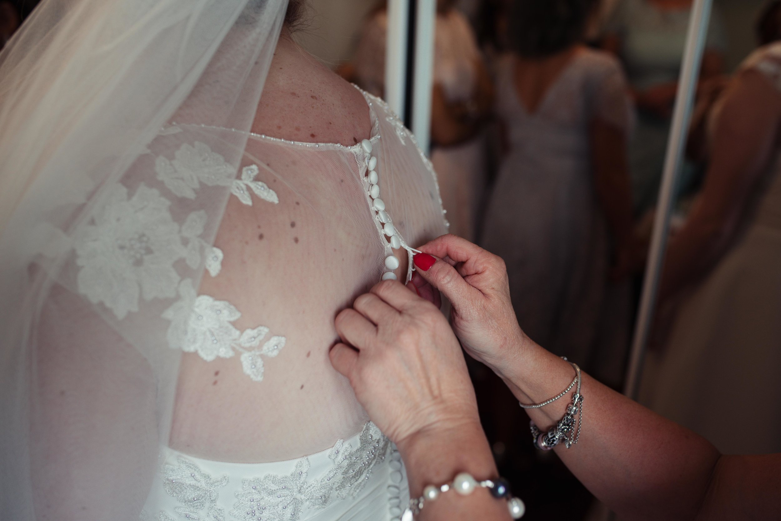 The bride is getting her dress buttoned up by her mother