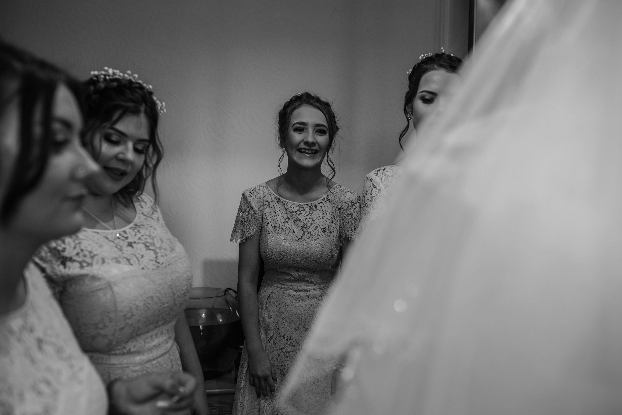 Bridesmaids stand and watch as the bride gets dressed for her wedding