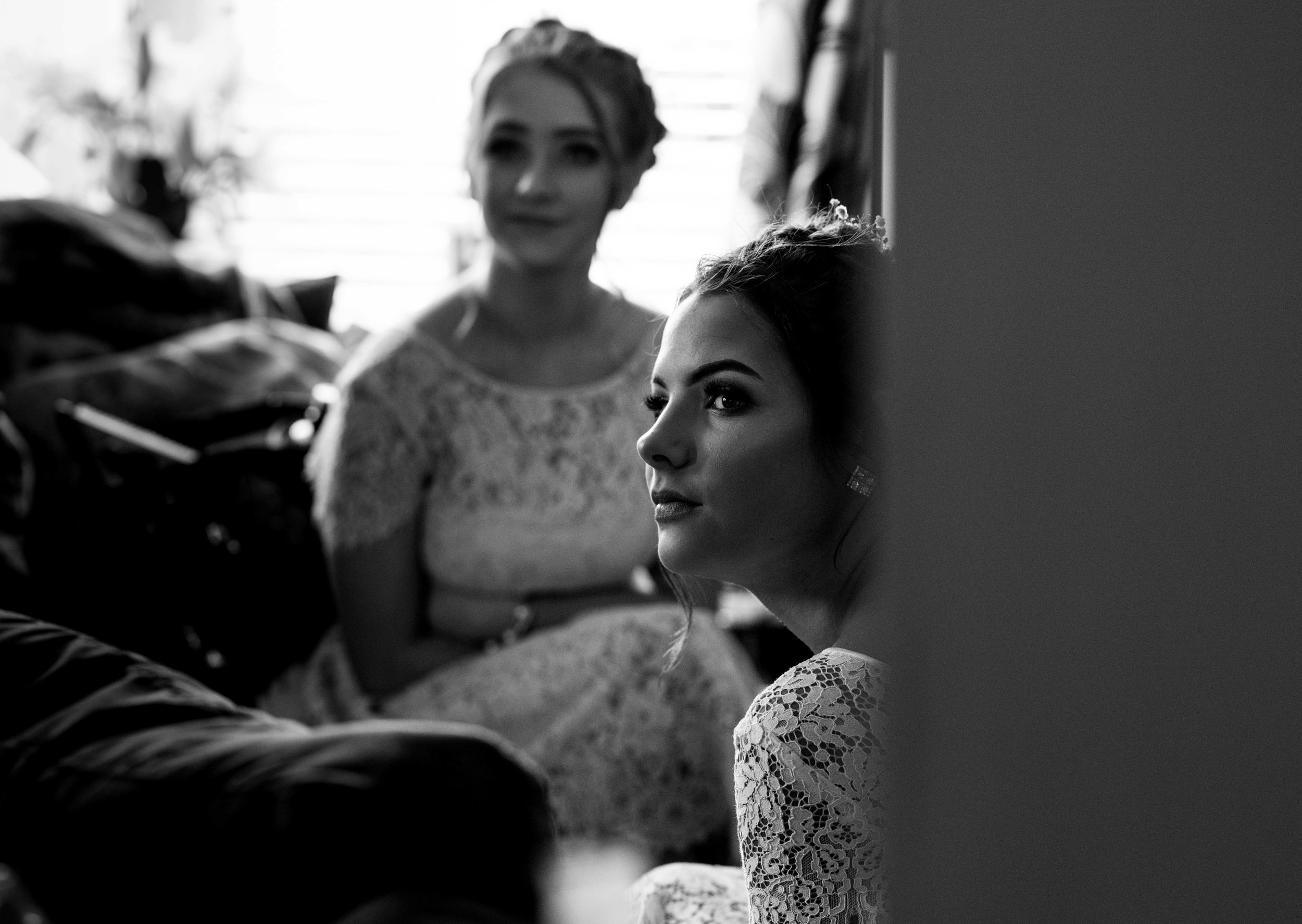 A bridesmaid sits and watches the bride coming down the stairs to her dad
