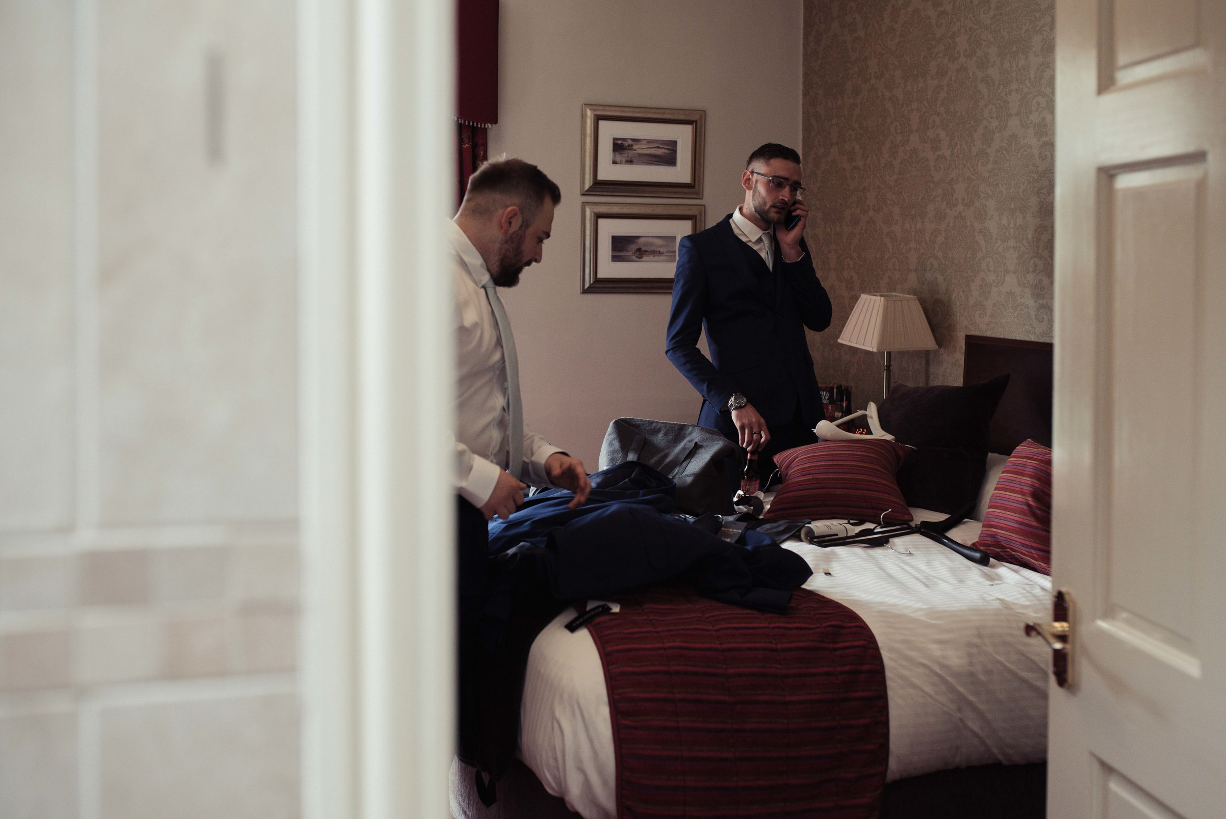 The best man makes a phone call as the groom gets ready