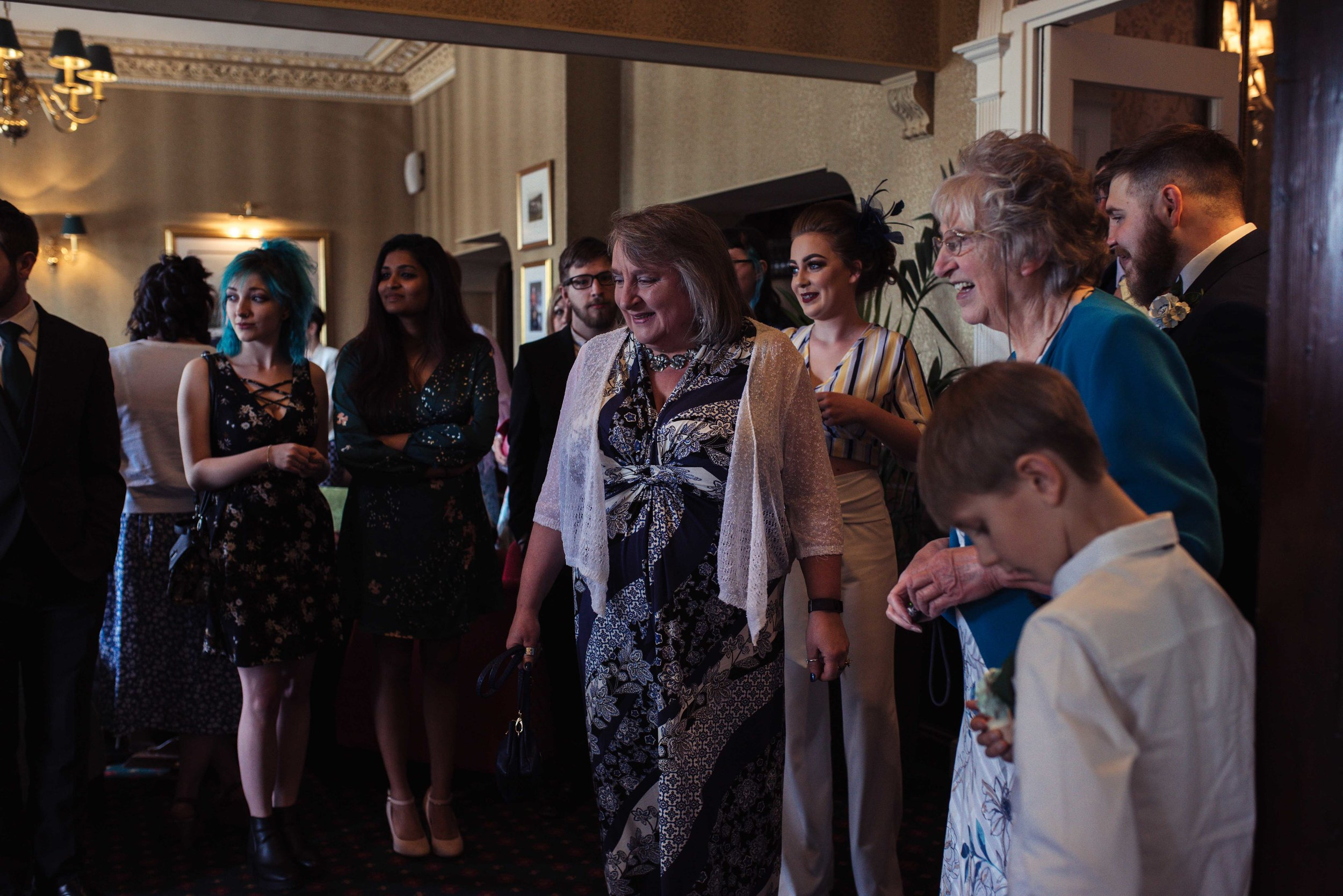 Wedding guests gather to see the groom in his suit for the first time