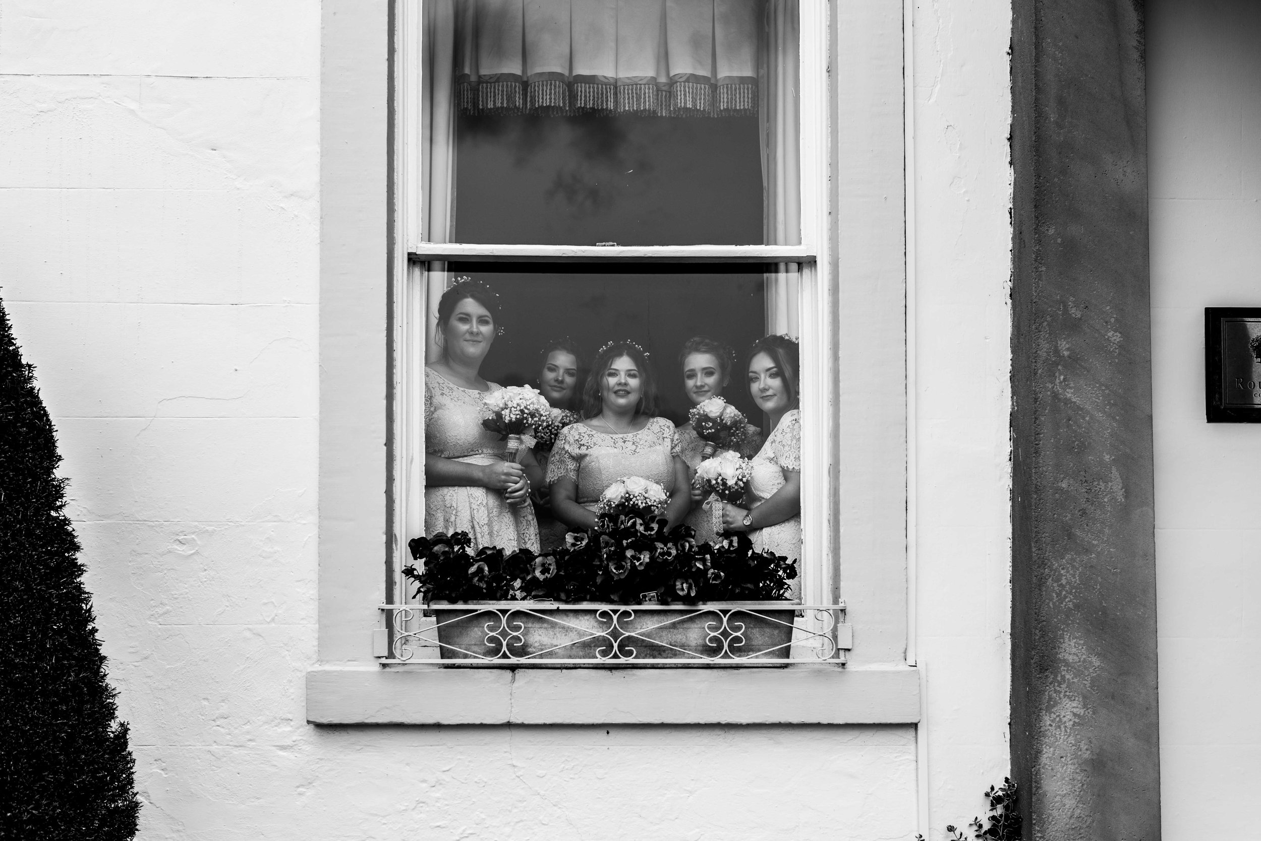 Bridesmaids stand at the window of the Roundthorn Country House and wait for the bride to arrive