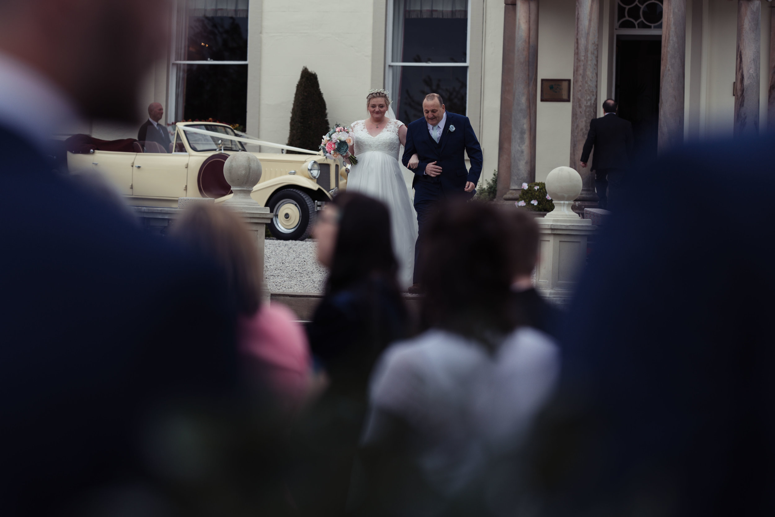 The bride and her father start to walk down the steps together