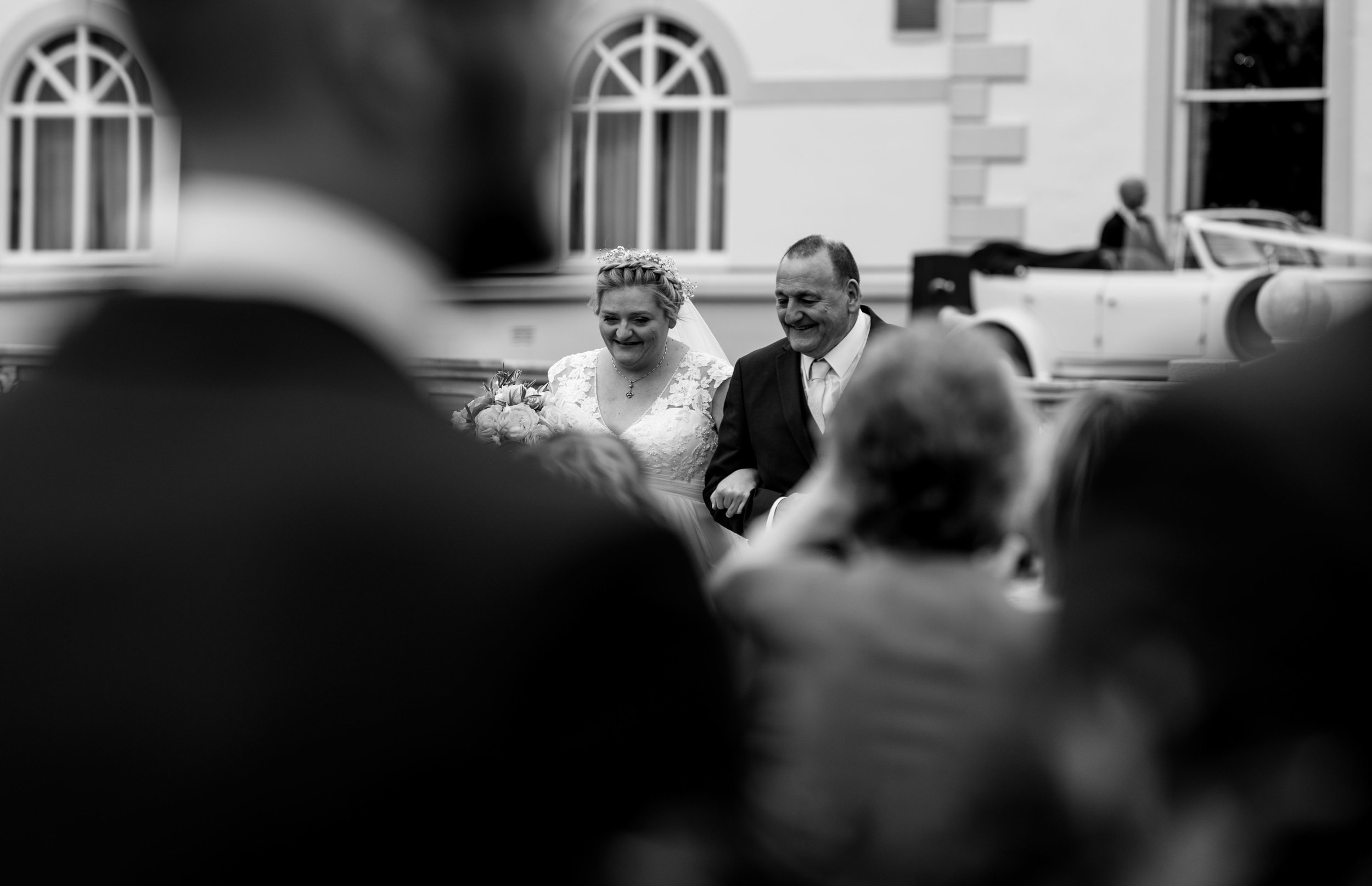 A smiling bride and her father walk down the path to the wedding ceremony