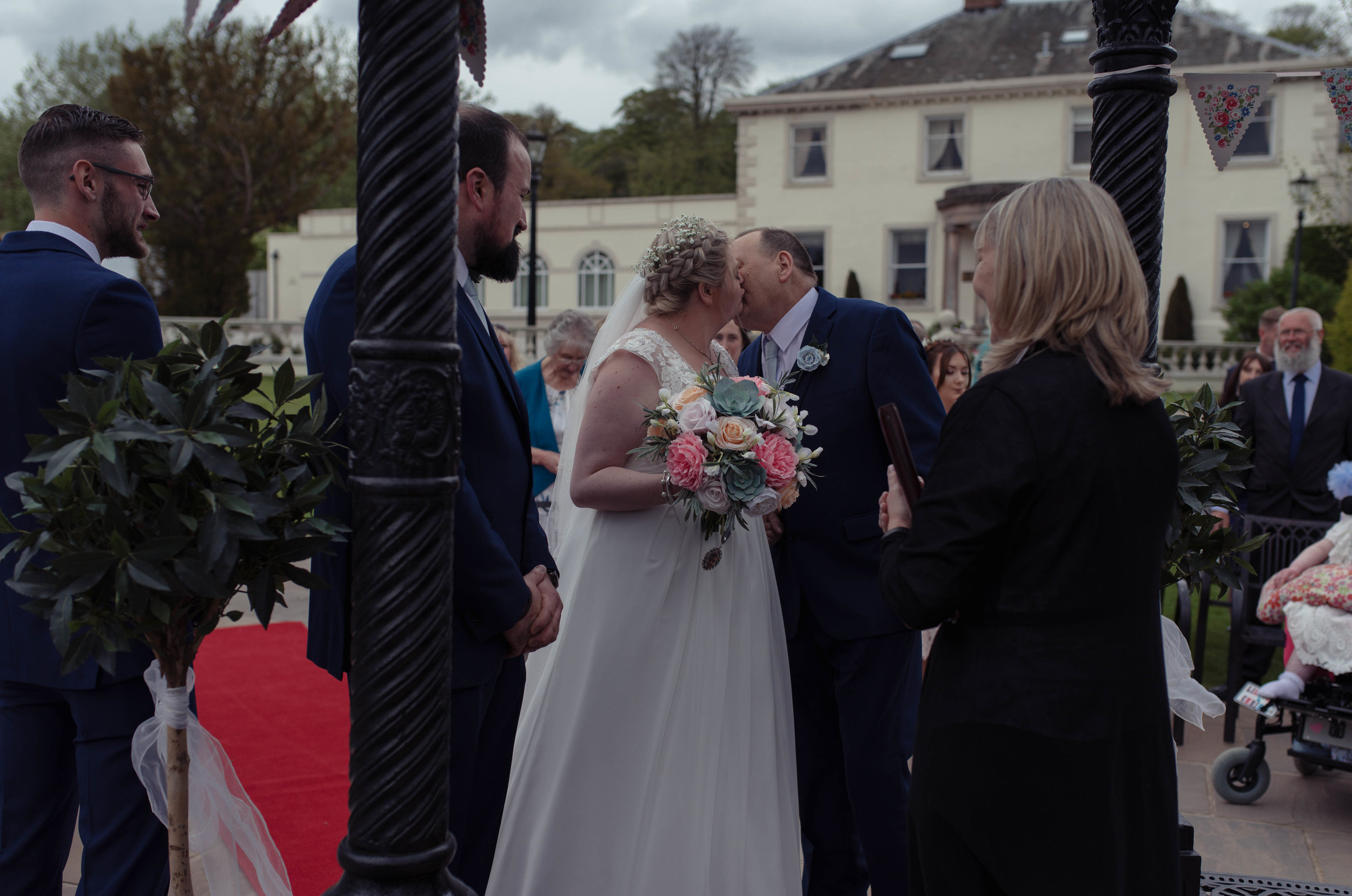 The bride and her father share a kiss as she gives him away