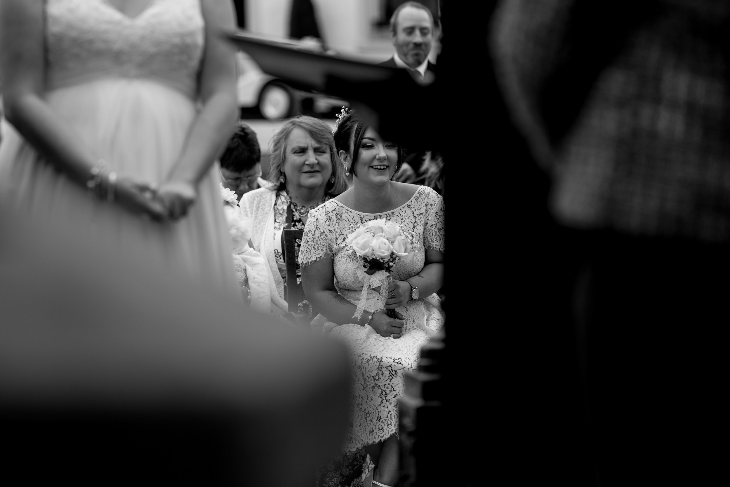 A bridesmaid sits smiling as the bride and groom exchange their vows