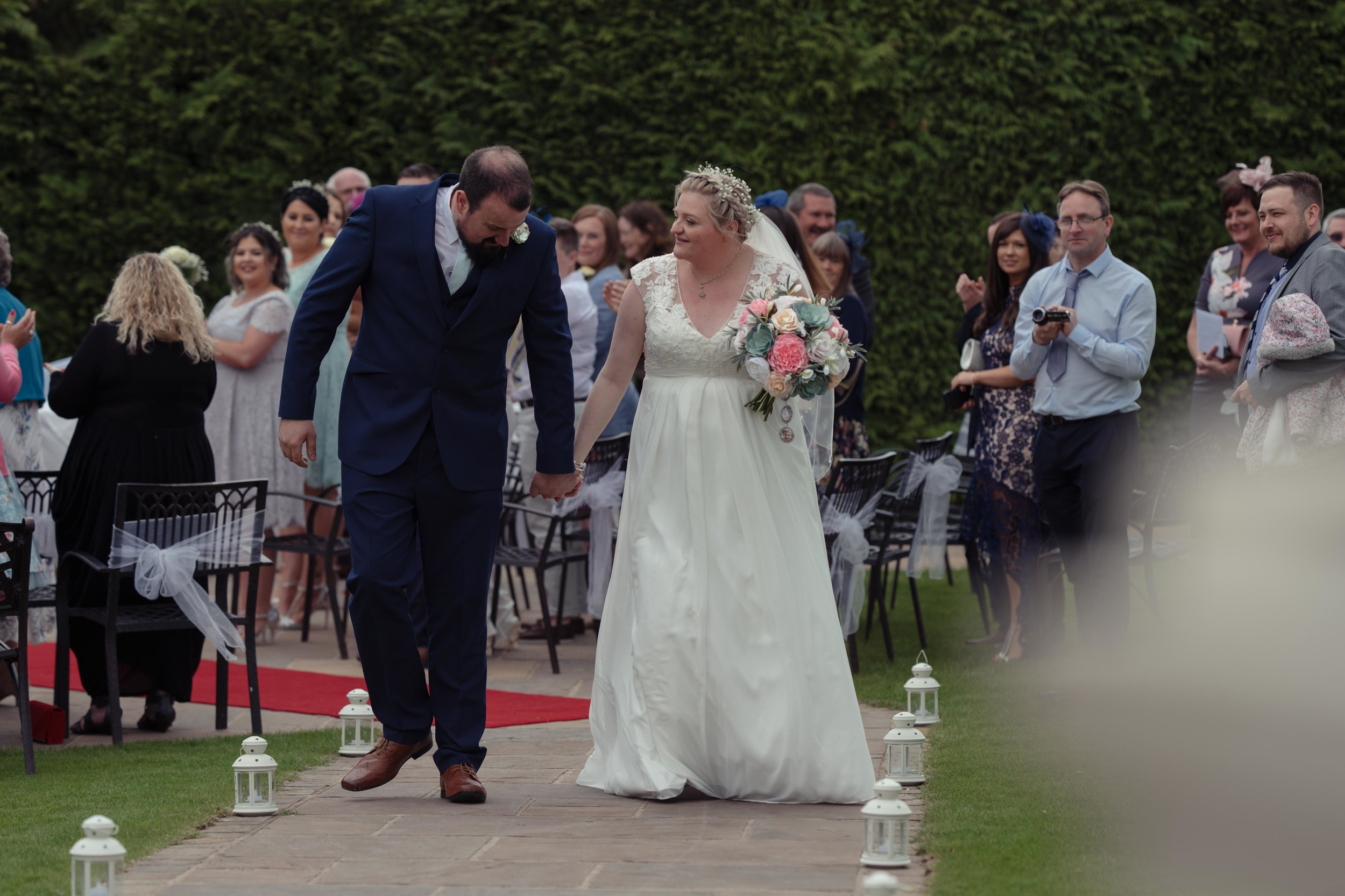 The bride and groom walk out from their wedding ceremony together