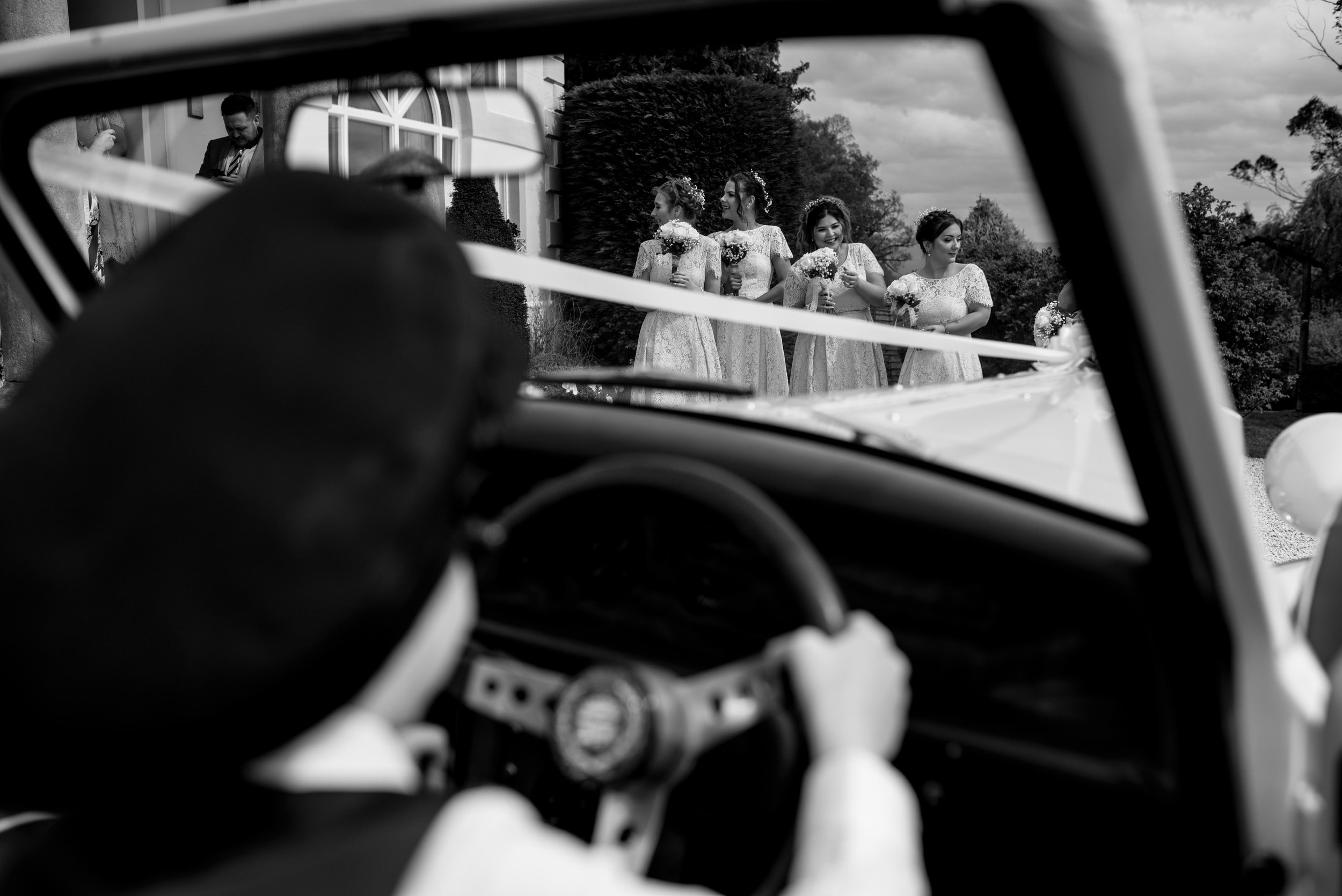 The bridesmaids are laughing as the page boy beeps the wedding car horn at them