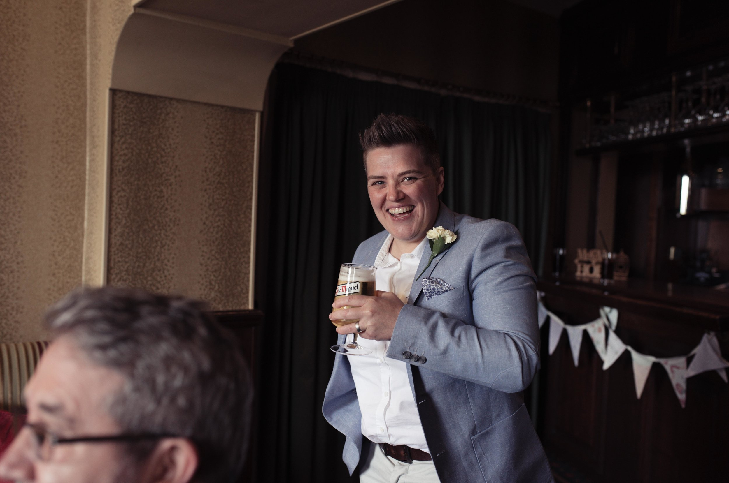 A wedding guest has a massive smile on her face in the bar of the wedding venue