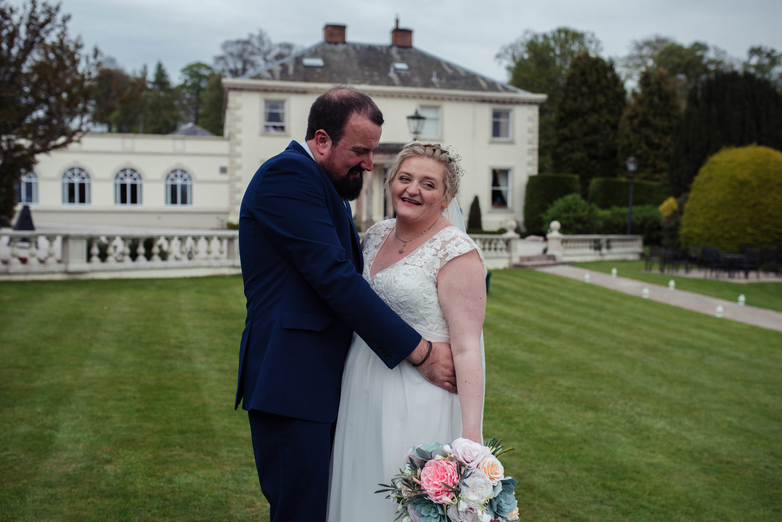 The bride and groom stand to have their photo taken outside the roundthorn country house