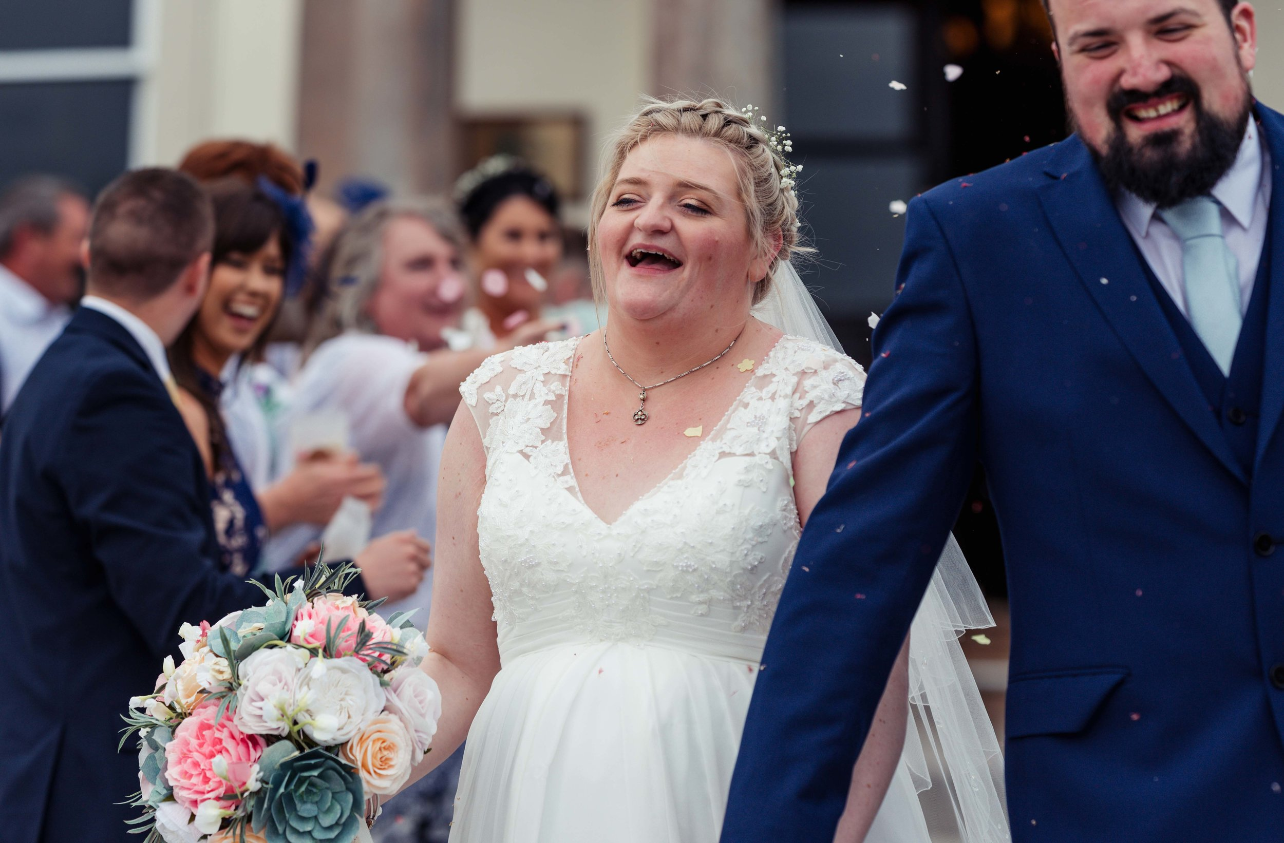 The bride at the end of their confetti photo, laughing her head off