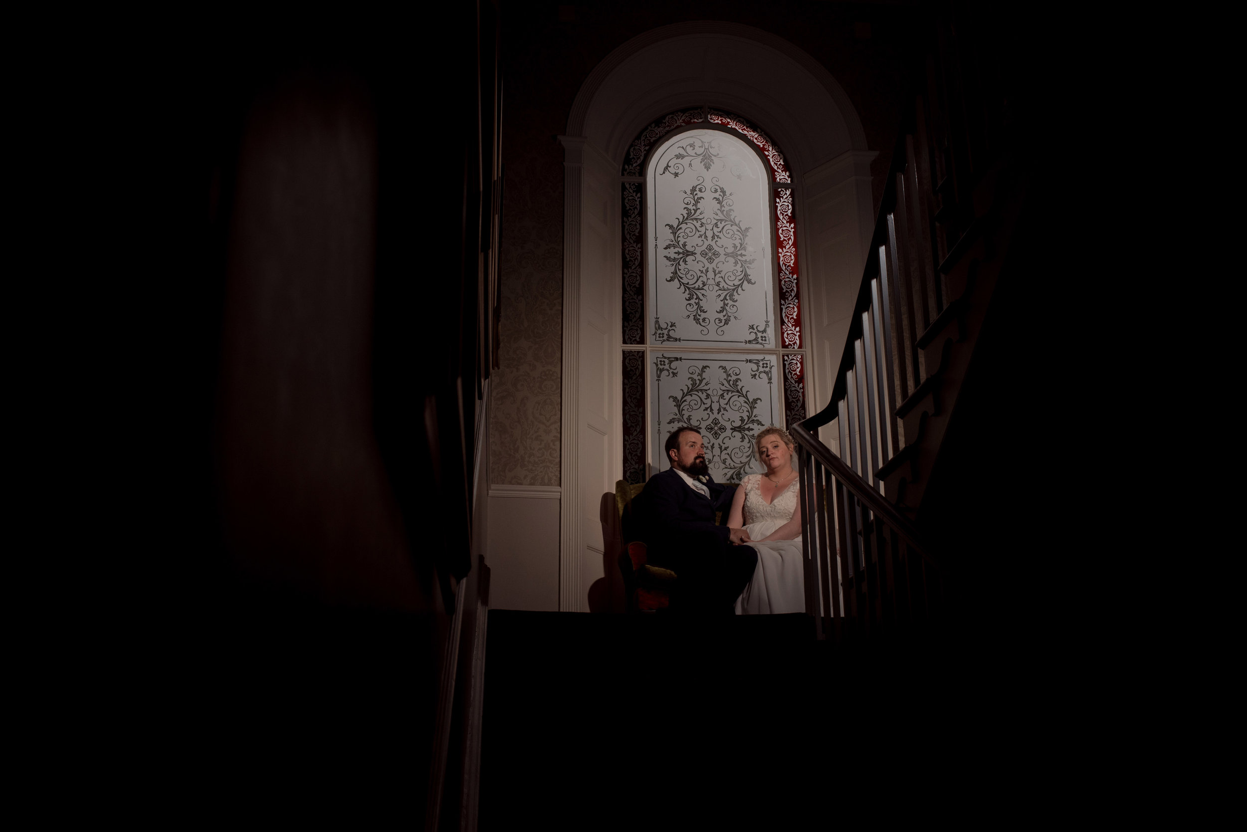 The bride and groom sit at the top of the stairs in their wedding venue and pose for a wedding photograph