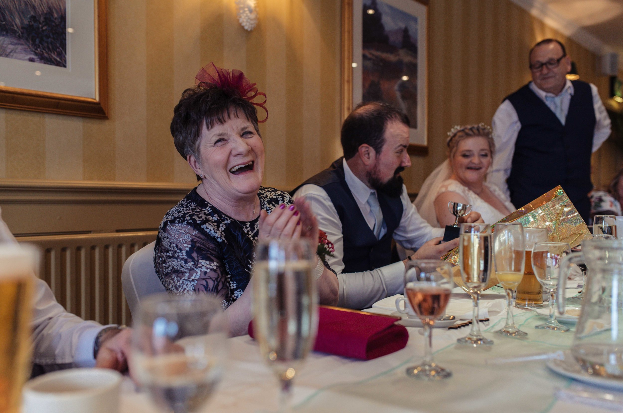 The grooms mother howls laughing during the speeches
