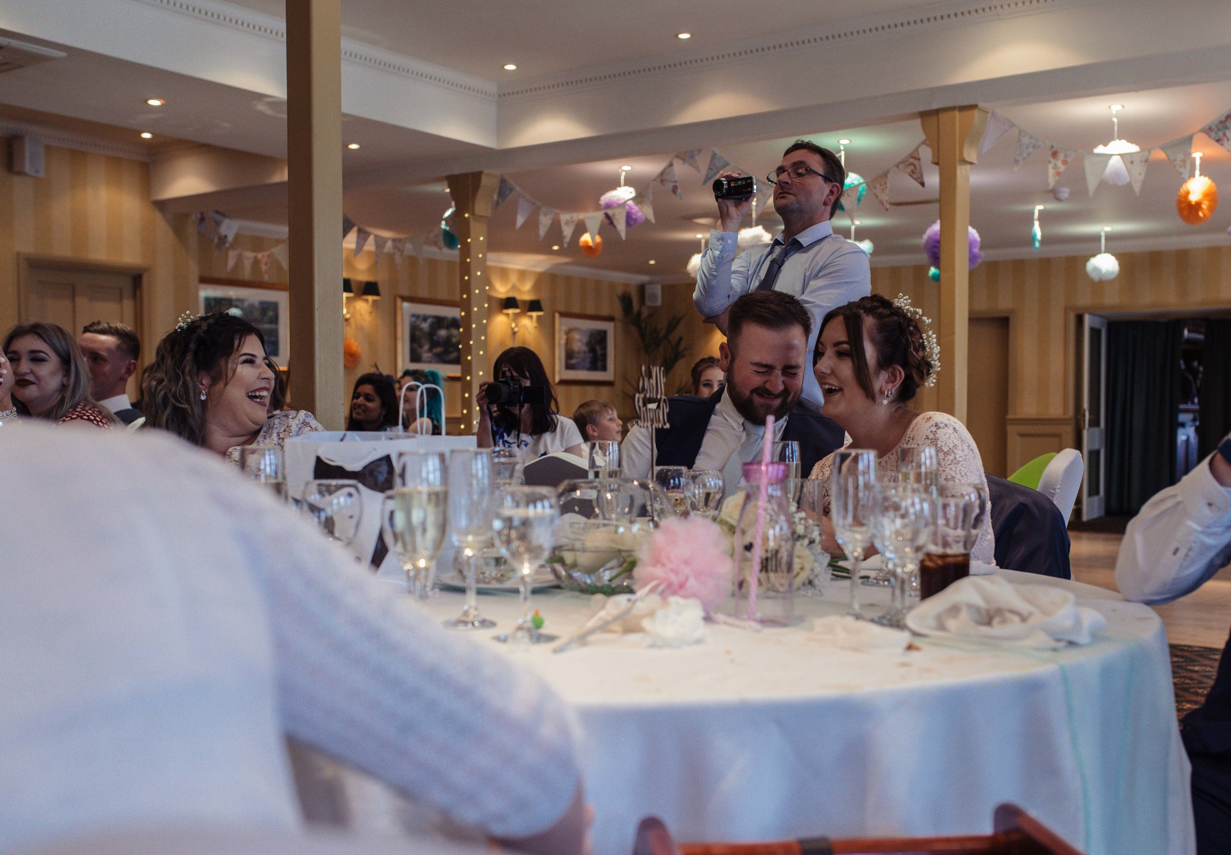 Two wedding guests laugh their heads off during the speeches