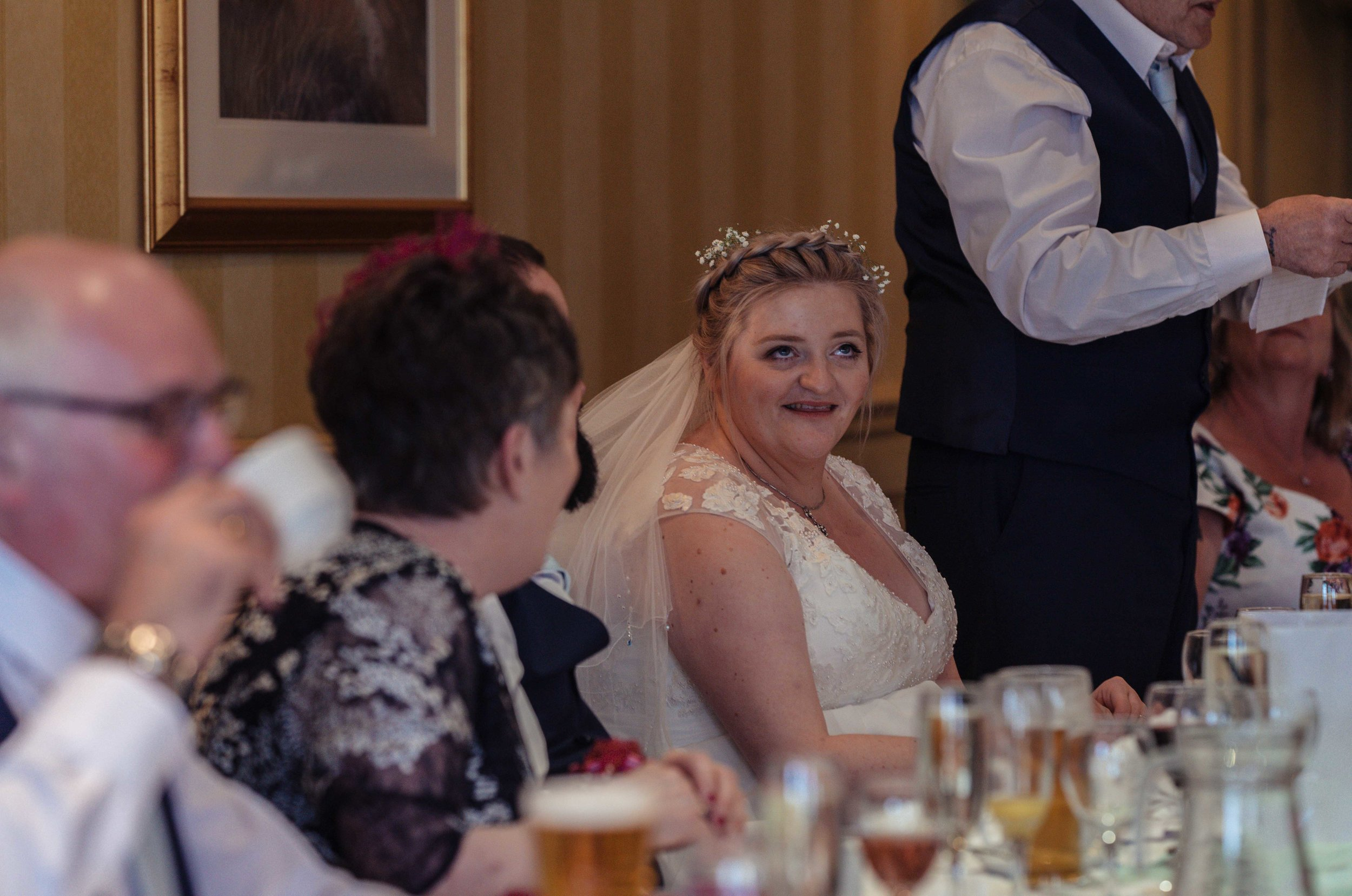 The bride waits for a joke during the wedding speeches