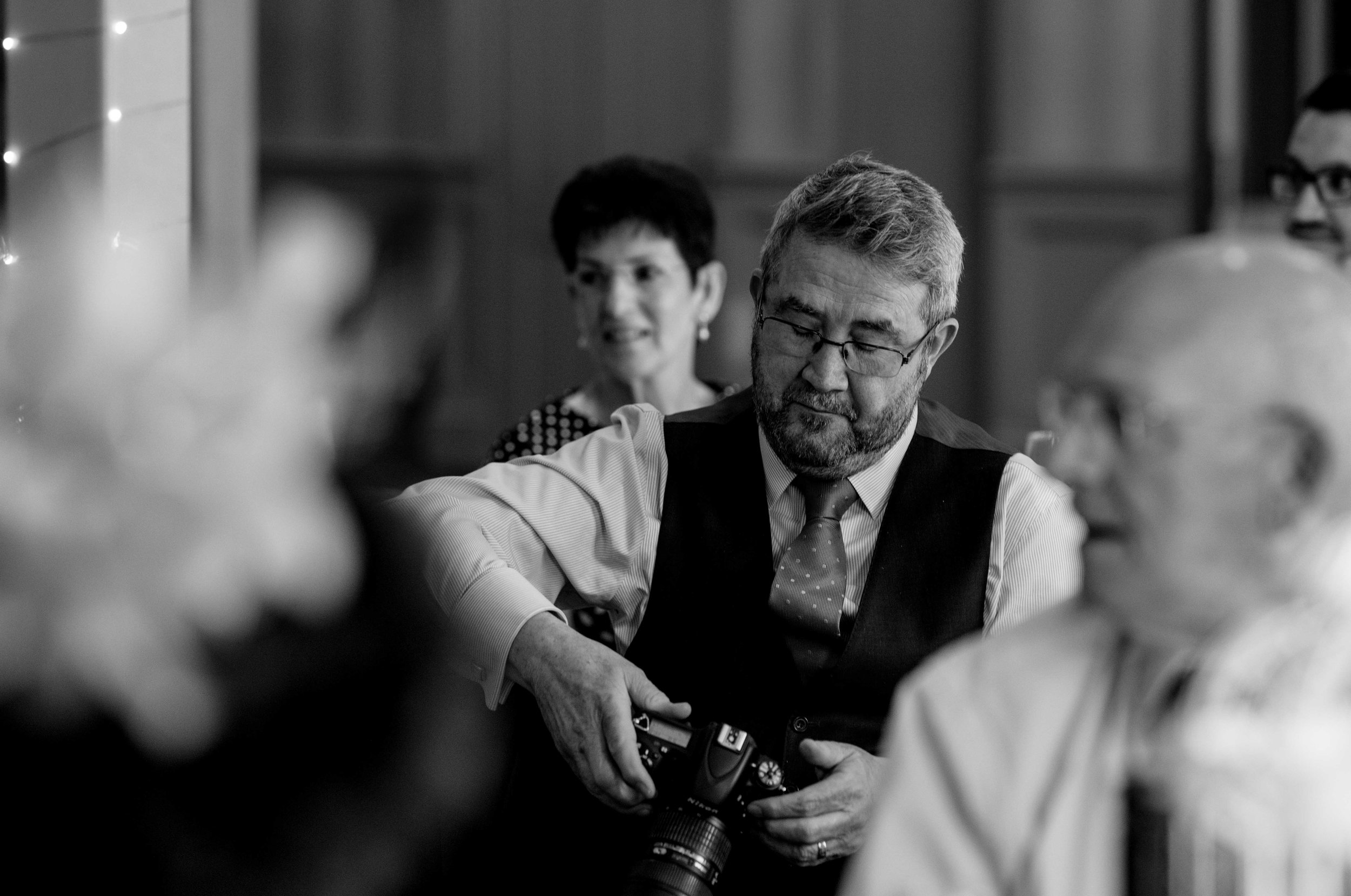 A wedding guest looks at his camera during the speeches
