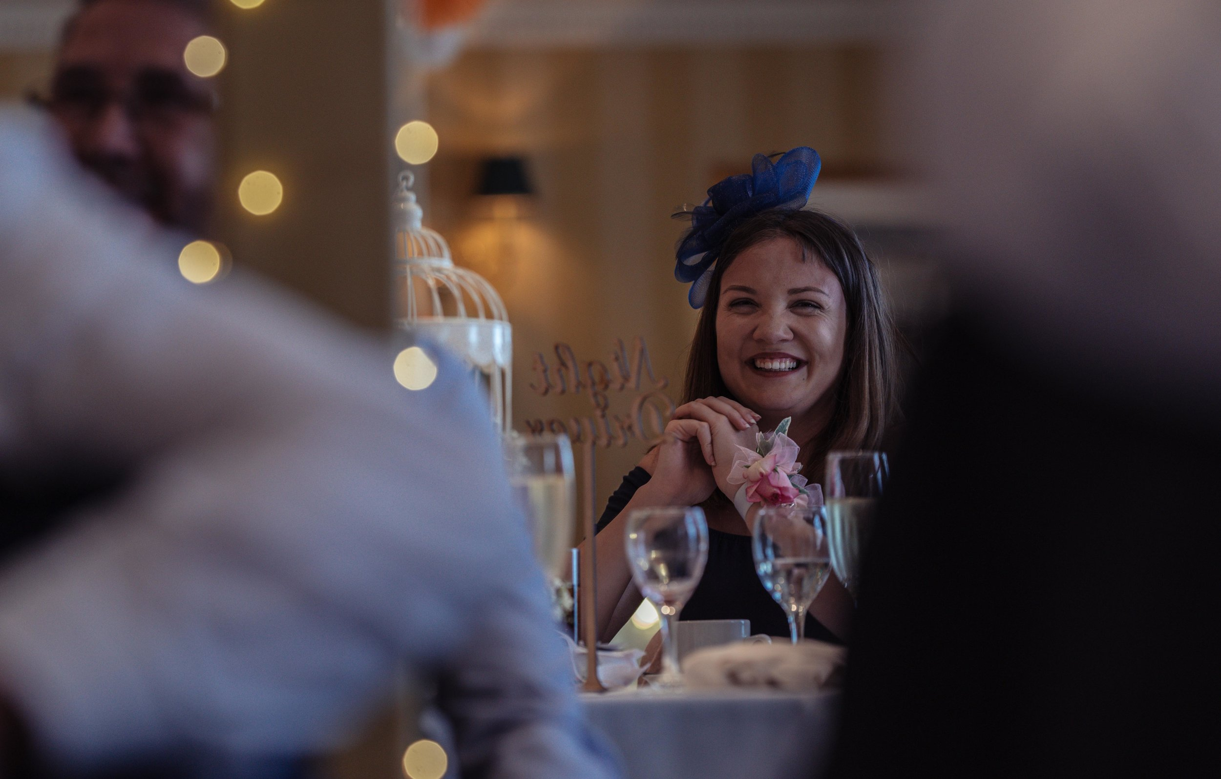 A wedding guest laughs at a joke during the speeches