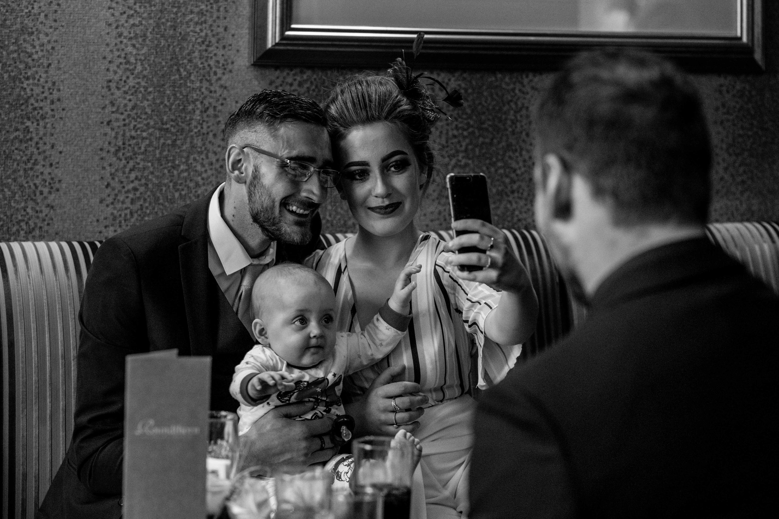 A young family pose for a selfie in the hotel bar