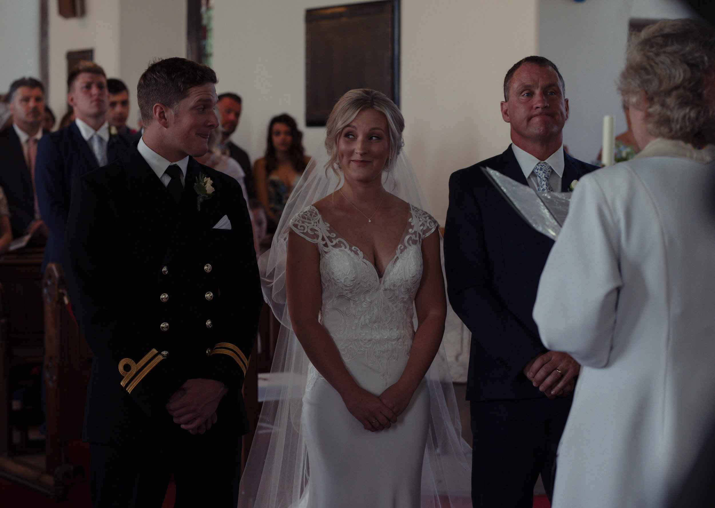 the bride and groom share a comedy glance with each other during the church ceremony