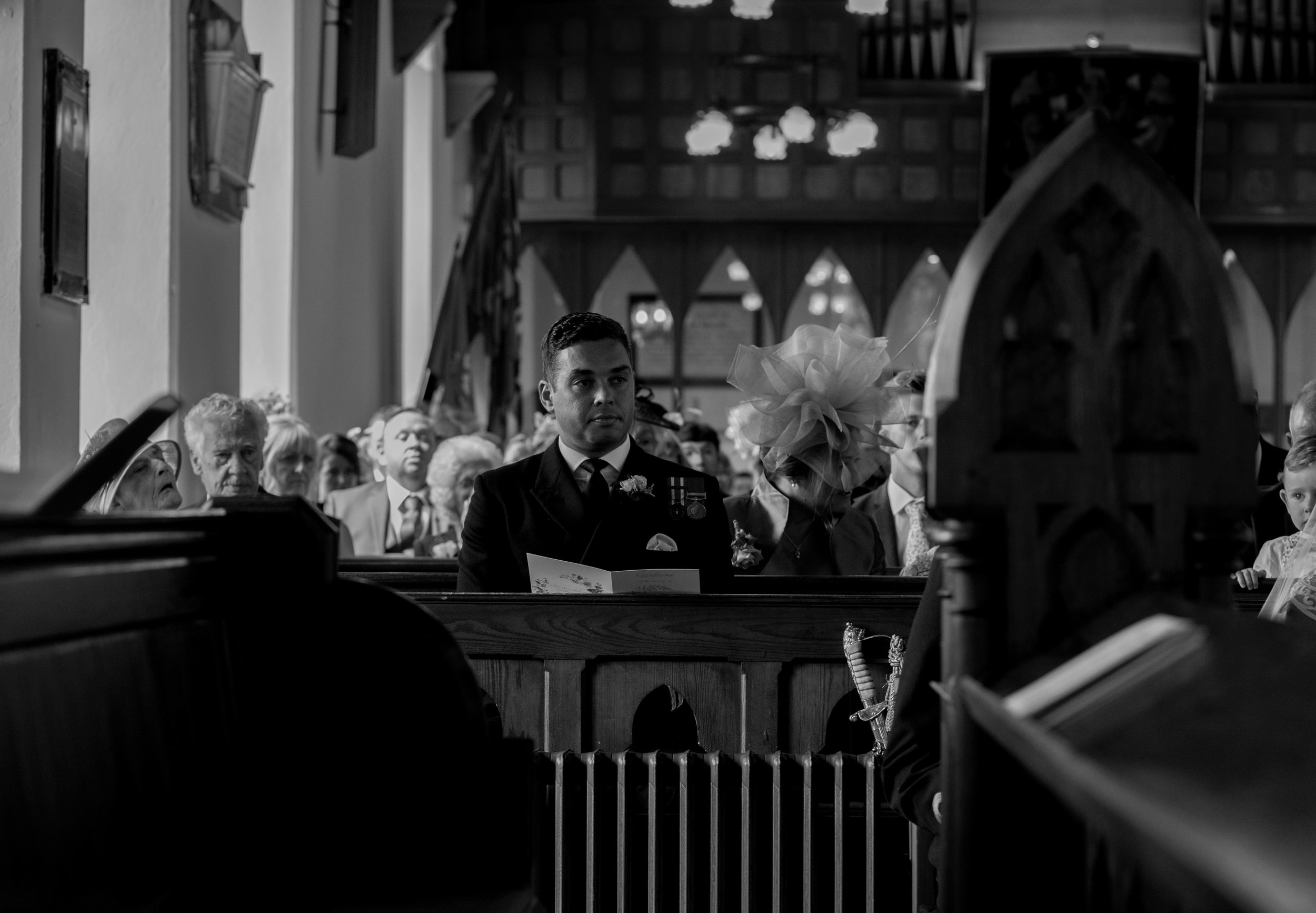the best man looks towards the couple as they exchange their vows in church
