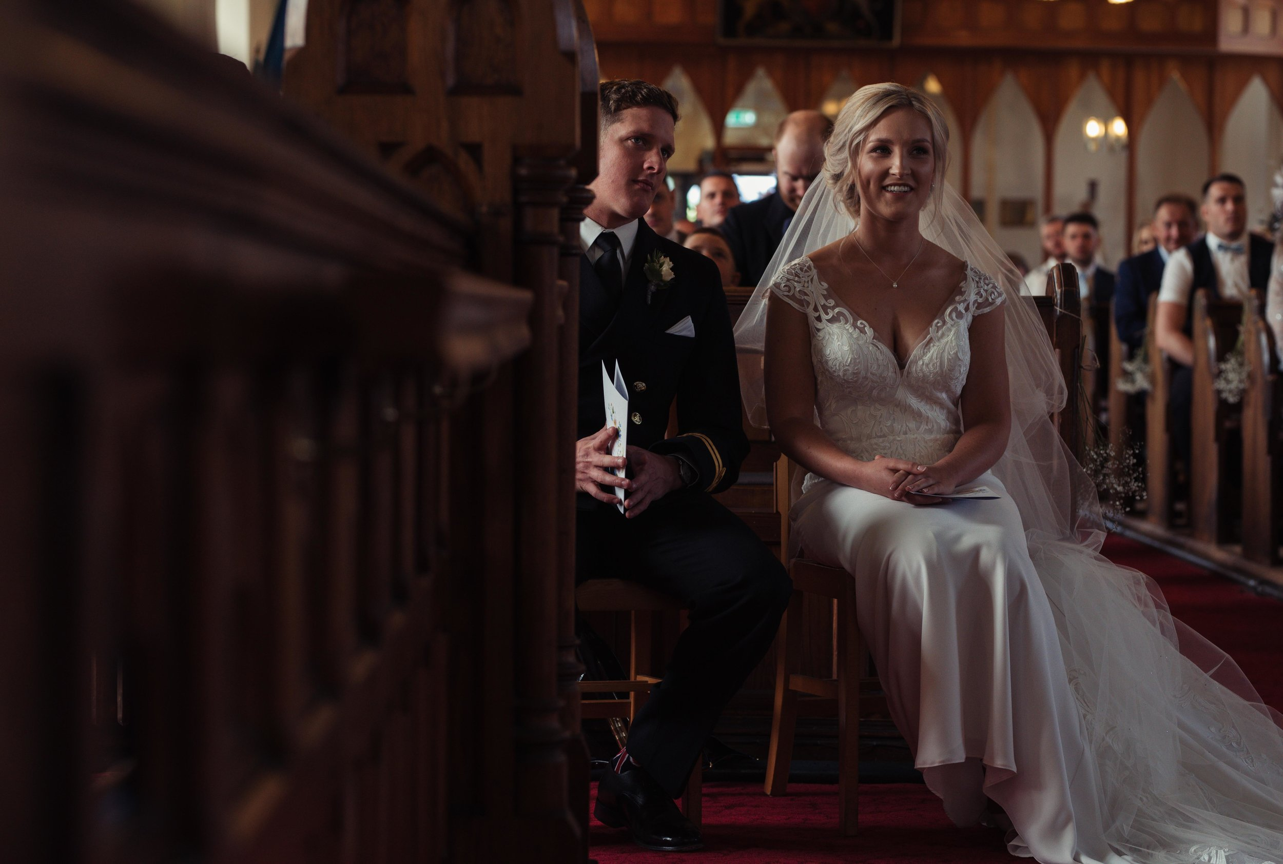 the bride and groom share a giggle over the vicars sermon during the wedding service