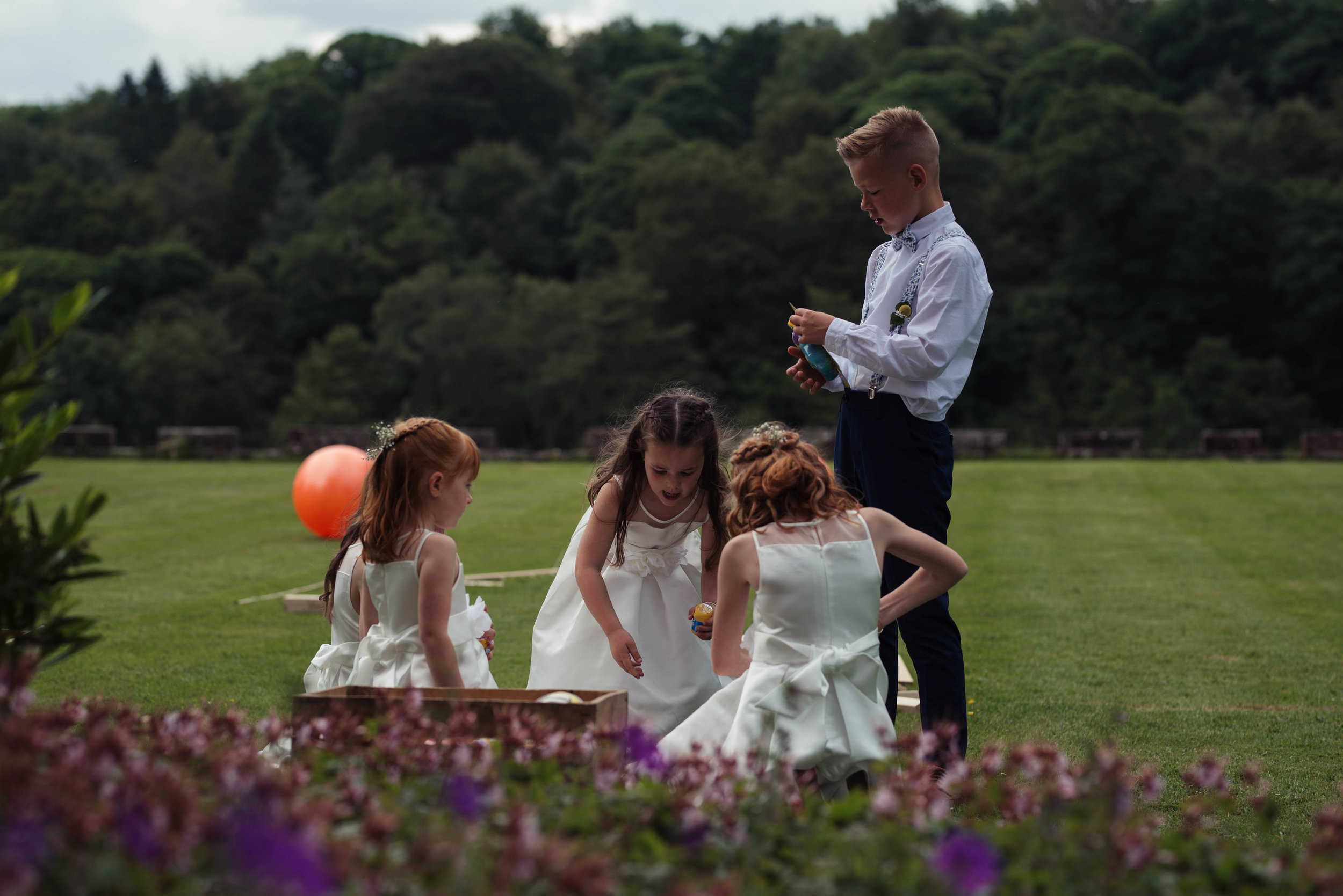 the flower girls and a page boy play lawn games at askham hall