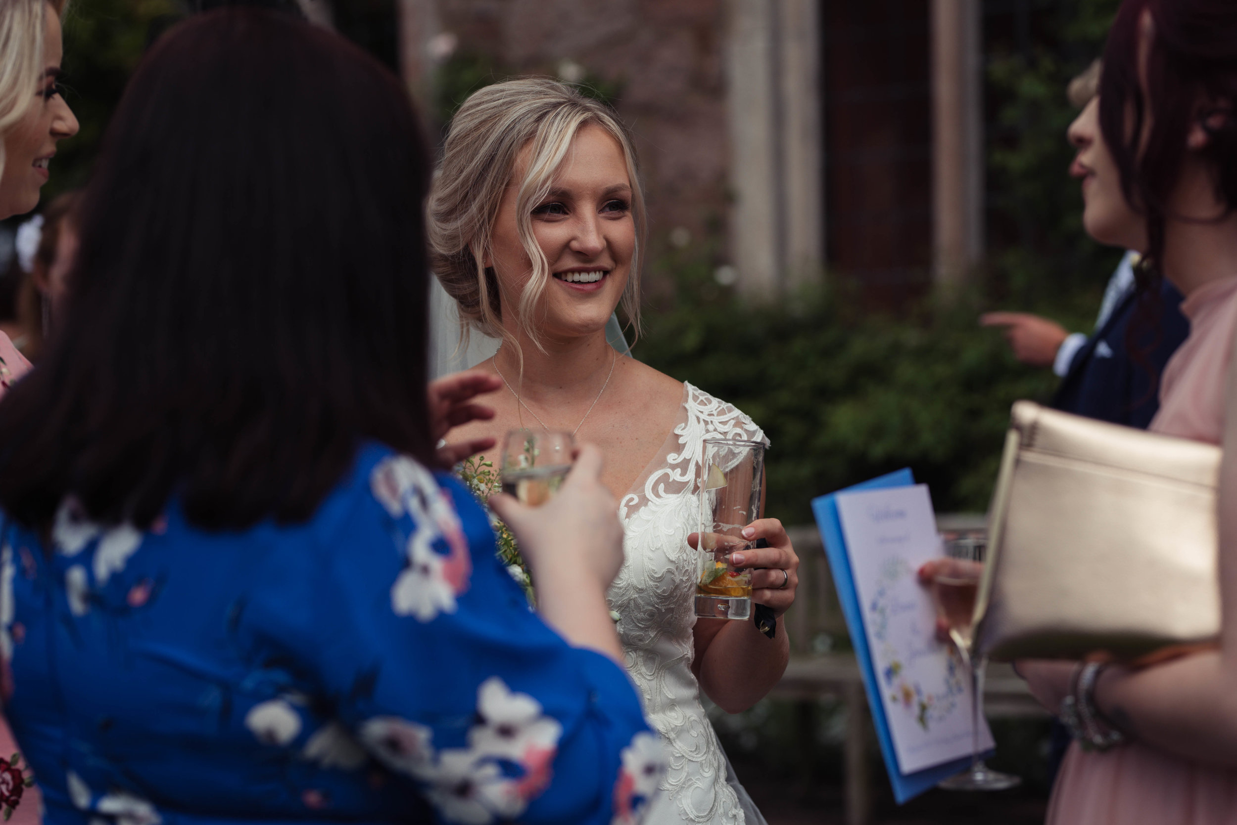 The bride chats to wedding guests during the drinks reception at Askham Hall