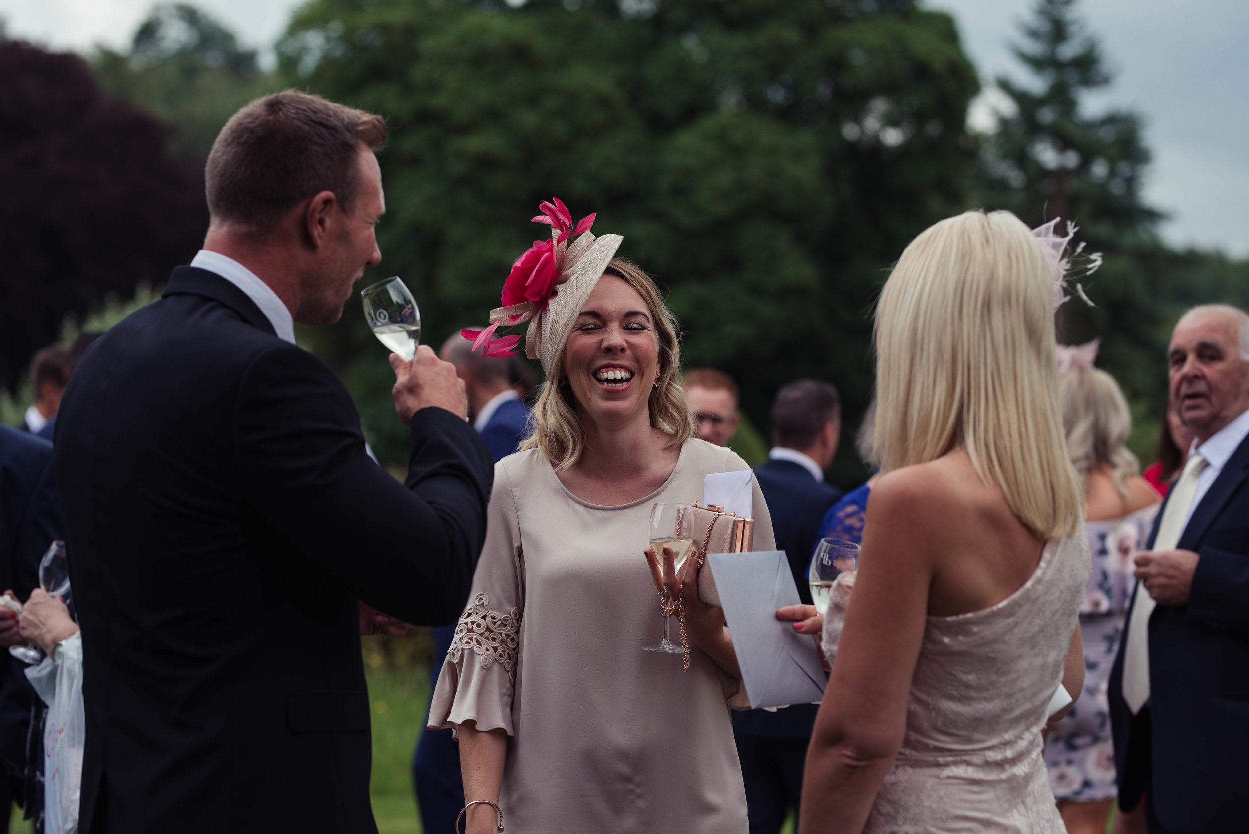A wedding guest has a giggle with members of her group during the drinks reception